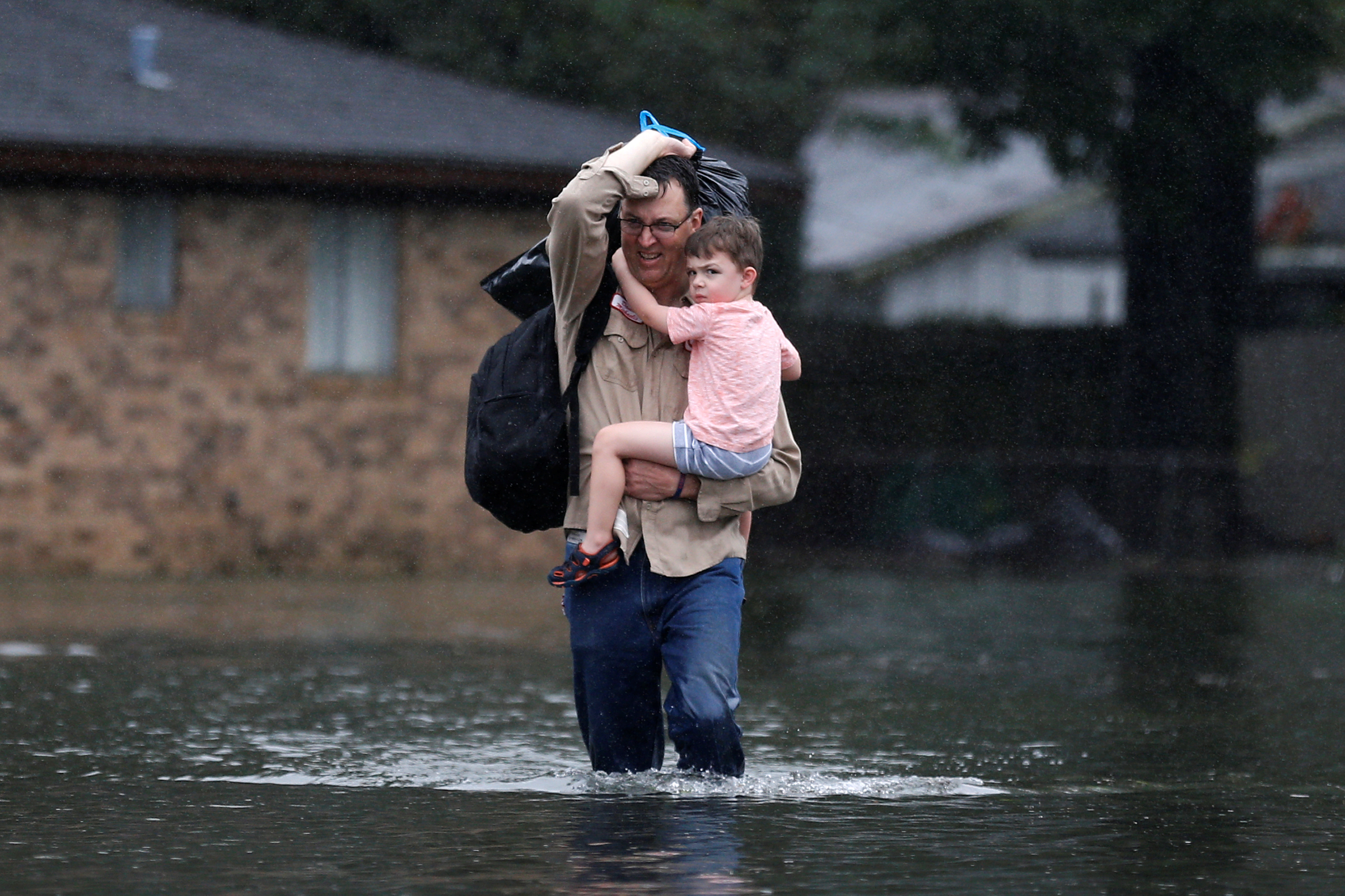 David Michaelis holds his 3-year-old grandson Teddy as he wades through flood waters from Tropical Storm Harvey in Orange, Texas, U.S., August 30, 2017. REUTERS/Jonathan Bachman