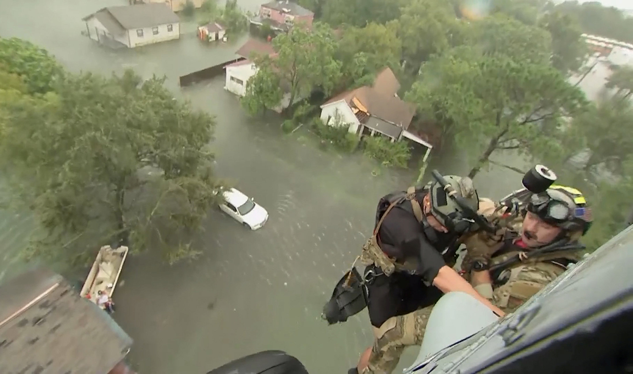 Two rescuers from U.S. Navy Helicopter Sea Combat Squadron 7 are lowered to a house after Tropical Storm Harvey flooded a neighborhood in Beaumont, Texas, U.S. in a still image from video August 30, 2017. U.S. Navy/Petty Officer 1st Class Ernest Scott/Handout via REUTERS