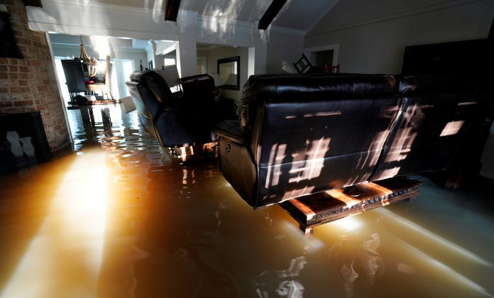 A family puts their belongings on furniture to keep them above floodwaters in their house from Harvey in Houston, Texas August 31, 2017
