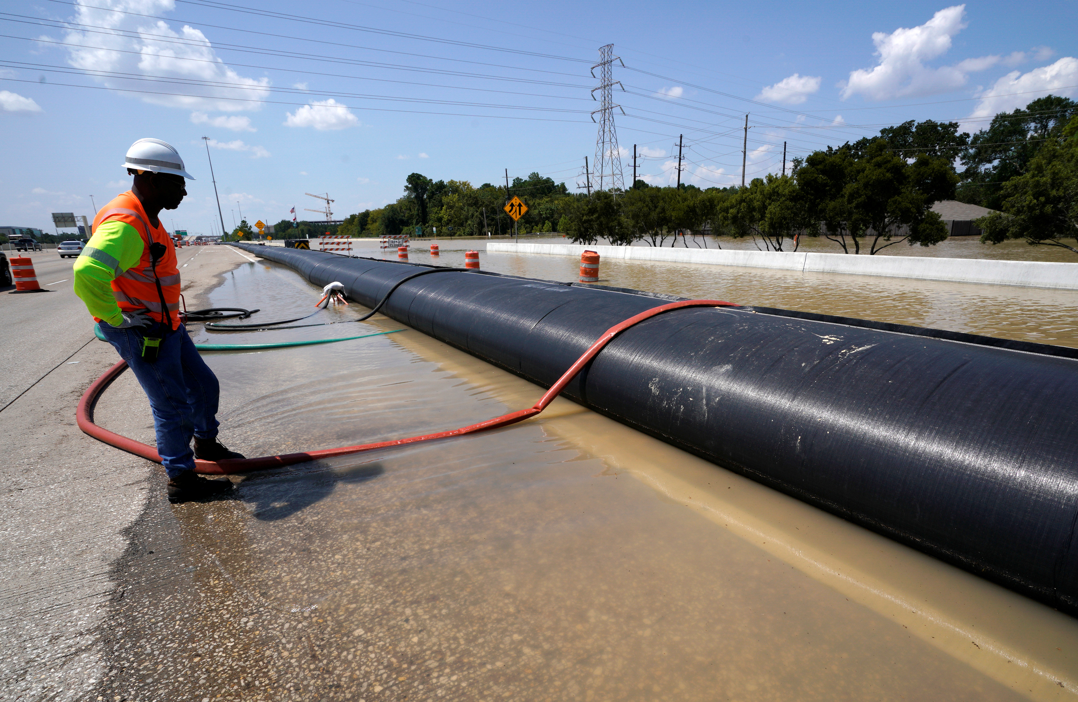 A Texas Department of Transportation worker monitors a temporary water filled dam keeping Harvey floodwaters from getting onto highway I-10 in Houston, Texas August 31, 2017.
