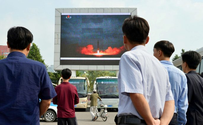 North Koreans watch a news report showing North Korea's Hwasong-12 intermediate-range ballistic missile launch