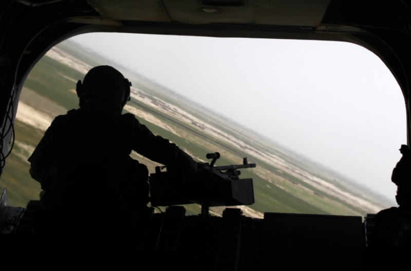 FILE PHOTO: The rear gunner of an Australian Chinook transport chopper mans a heavy machine gun during a low flight over the Arghandab valley in Kandahar province, southern Afghanistan, May 3, 2010. REUTERS/Yannis Behrakis