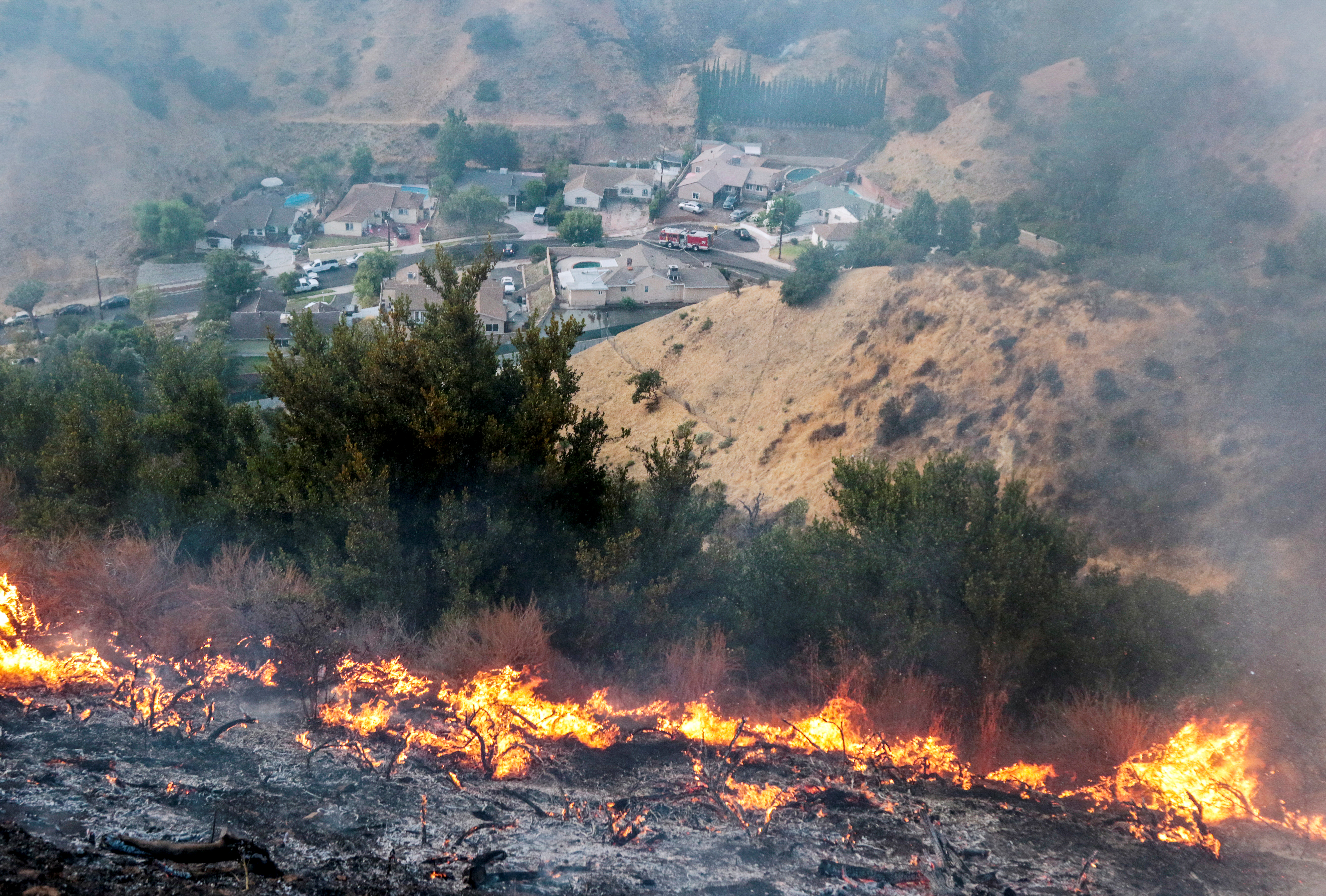 Flames above houses in Sun Valley during the La Tuna Canyon fire over Burbank, California, U.S., September 2, 2017.