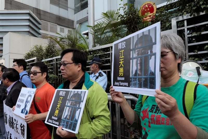 FILE PHOTO: Pro-democracy demonstrators hold up portraits of Chinese disbarred lawyer Jiang Tianyong, demanding his release, during a demonstration outside the Chinese liaison office in Hong Kong, China December 23, 2016. REUTERS/Tyrone Siu