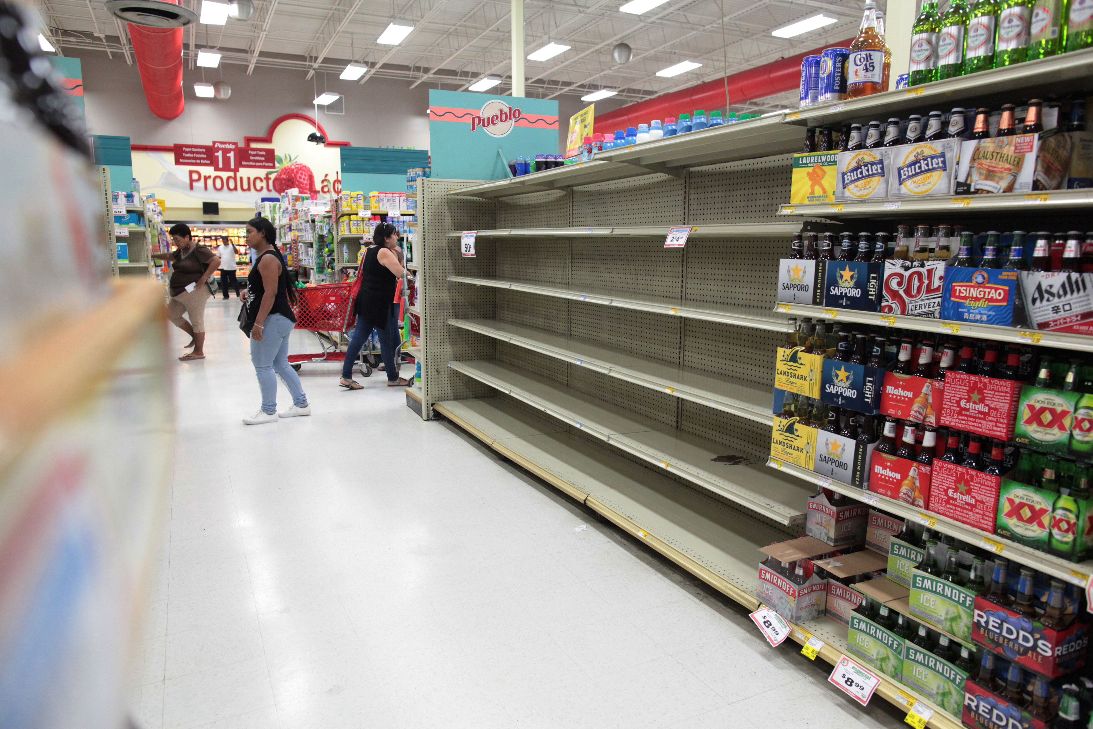 Customers walk near empty shelves that are normally filled with bottles of water after Puerto Rico Governor Ricardo Rossello declared a state of emergency in preparation for Hurricane Irma, in San Juan, Puerto Rico September 4, 2017. REUTERS/Alvin Baez