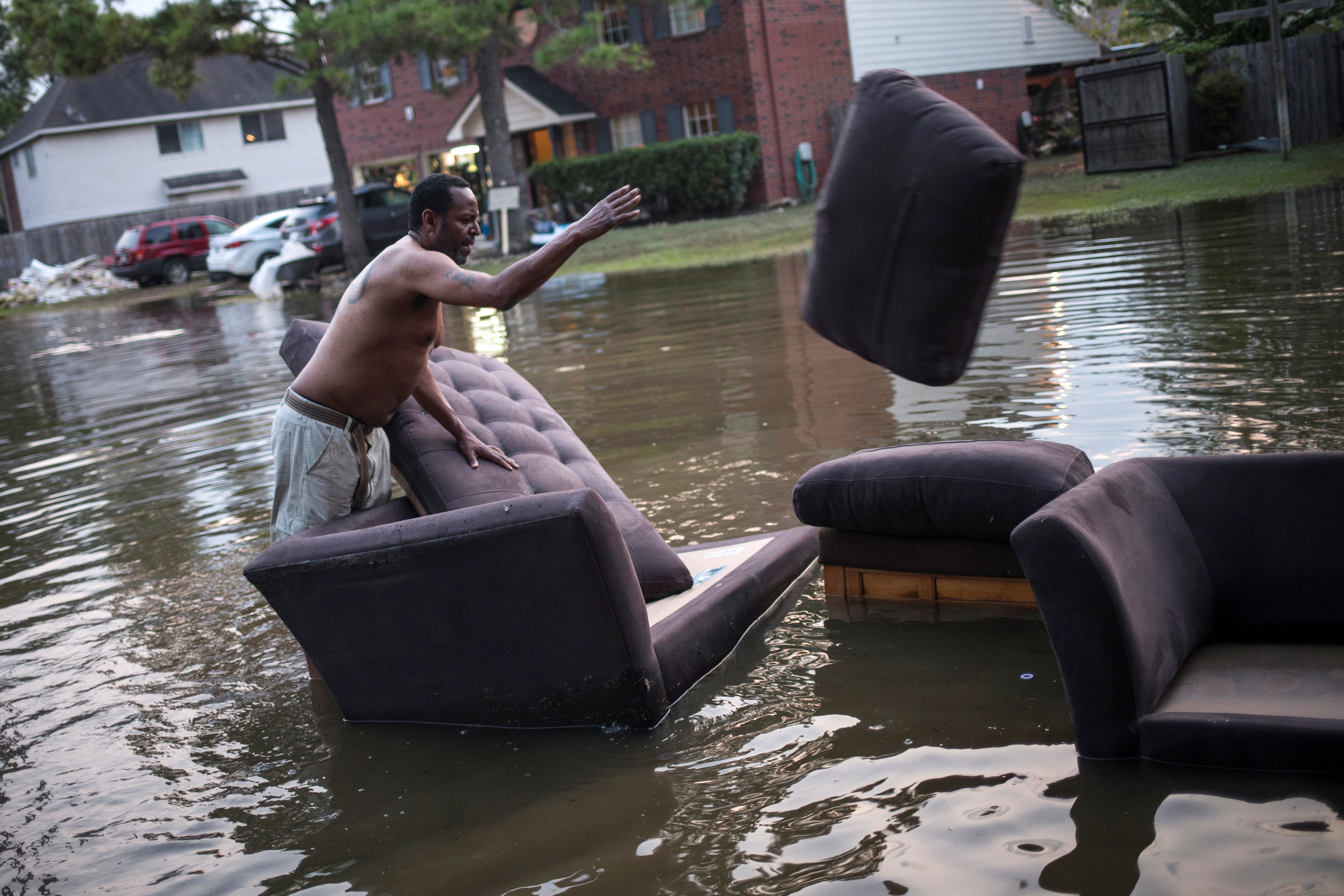 Vince Ware moves his sofas onto the sidewalk from his house which was left flooded from Tropical Storm Harvey in Houston, Texas. REUTERS/Adrees Latif