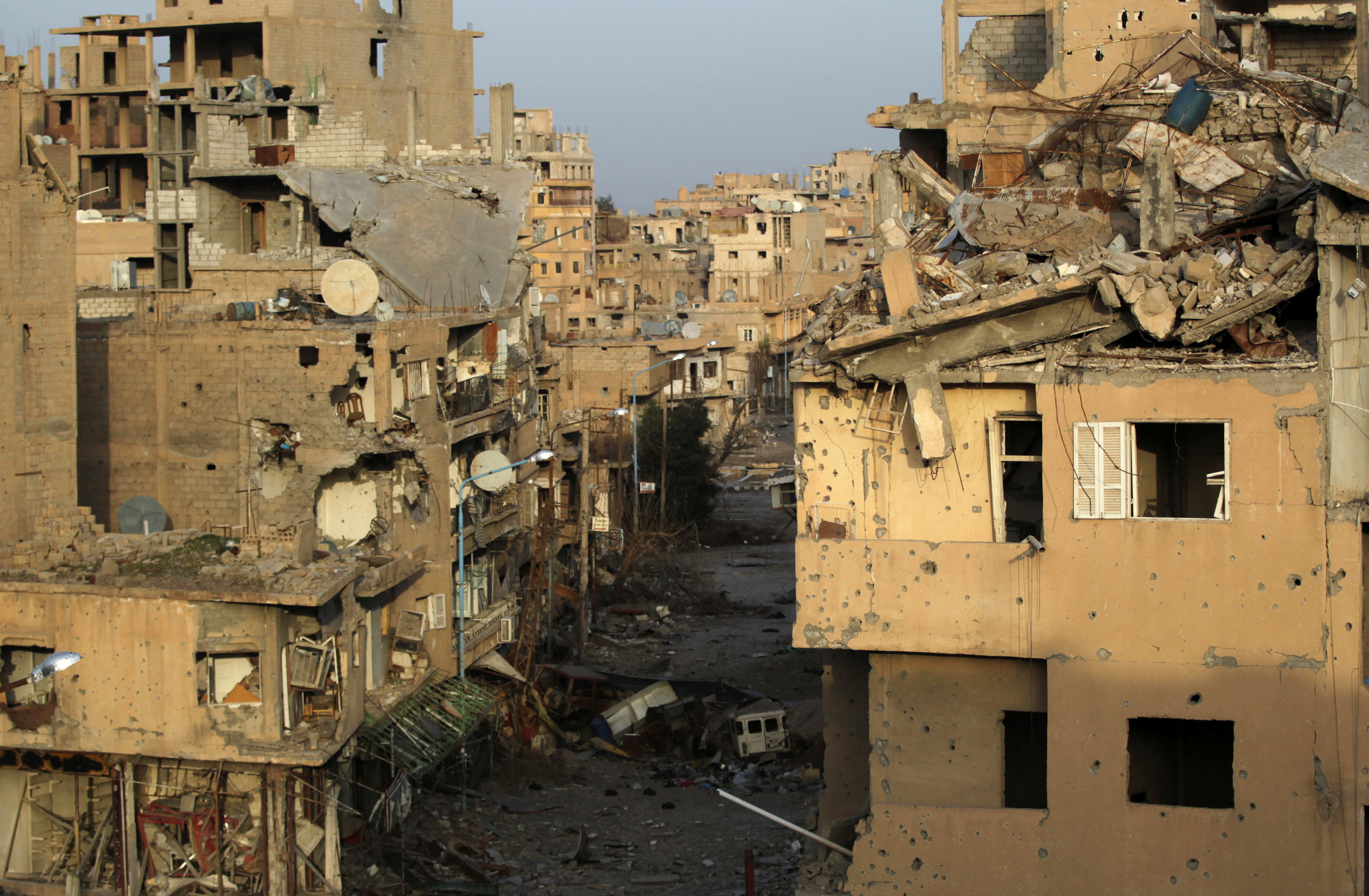 FILE PHOTO: A view shows damaged buildings in Deir al-Zor, eastern Syria February 19, 2014. REUTERS/Khalil Ashawi/File Photo
