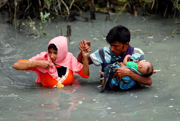 Rohingya refugees carry their child as they walk through water after crossing border by boat through the Naf River in Teknaf, Bangladesh, September 7, 2017. REUTERS/Mohammad Ponir Hossain