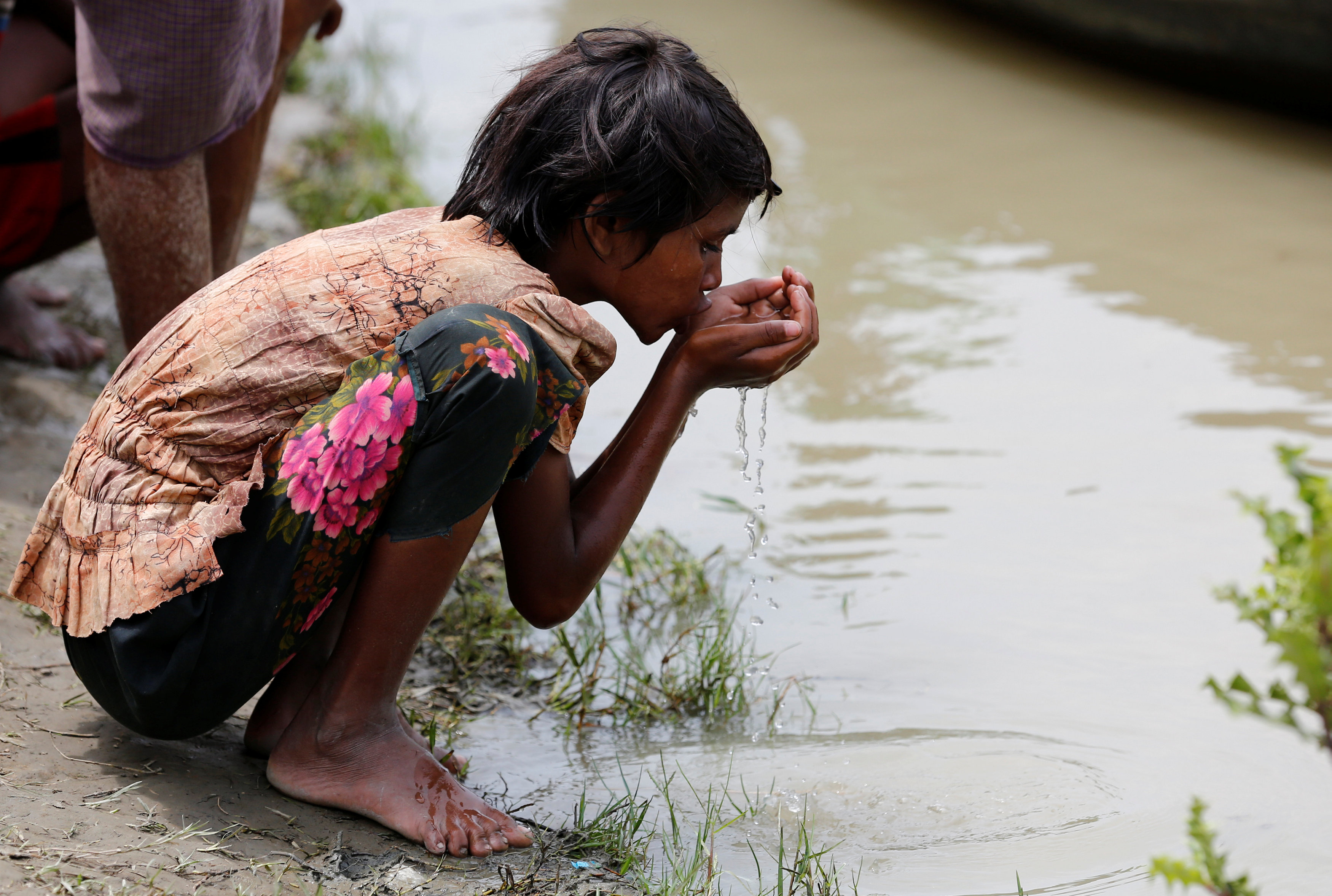 A Rohingya refugee girl drinks river water as she waits for boat to cross the border through Naf river in Maungdaw, Myanmar, September 7, 2017.REUTERS/Mohammad Ponir Hossain