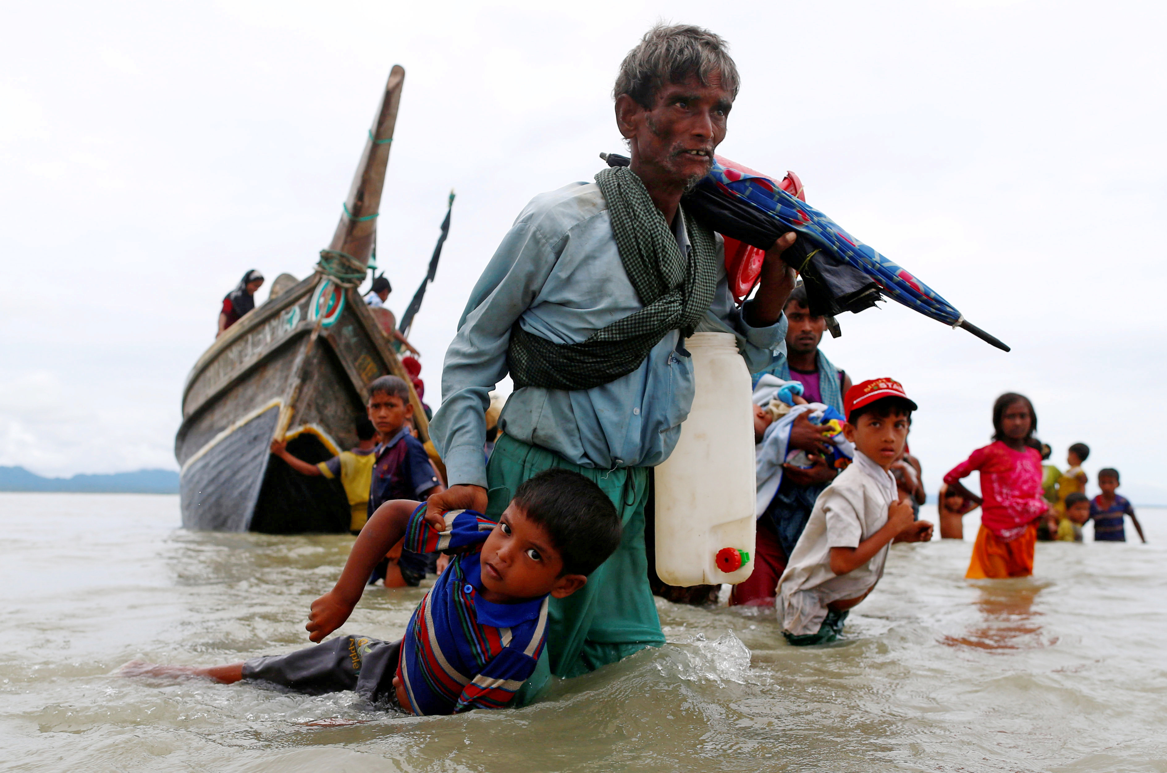 A Rohingya refugee man pulls a child as they walk to the shore after crossing the Bangladesh-Myanmar border by boat through the Bay of Bengal in Shah Porir Dwip, Bangladesh, September 10, 2017. REUTERS/Danish Siddiqui