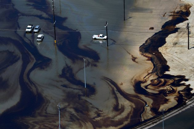 Vehicles sit amid leaked fuel mixed in with flood waters caused by Tropical Storm Harvey in the parking lot of Motiva Enterprises LLC in Port Arthur, Texas, U.S. August 31, 2017.