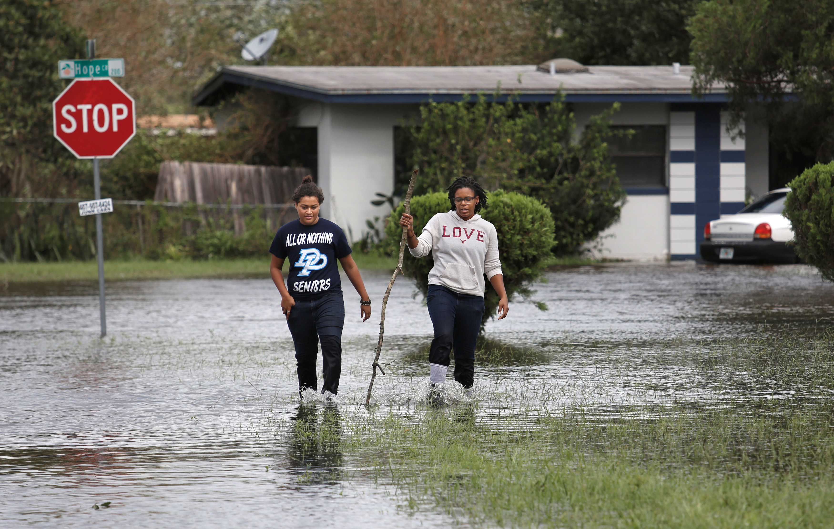 Residents walk through flood waters left in the wake of Hurricane Irma in a suburb of Orlando, Florida, U.S., September 11, 2017. REUTERS/Gregg Newton