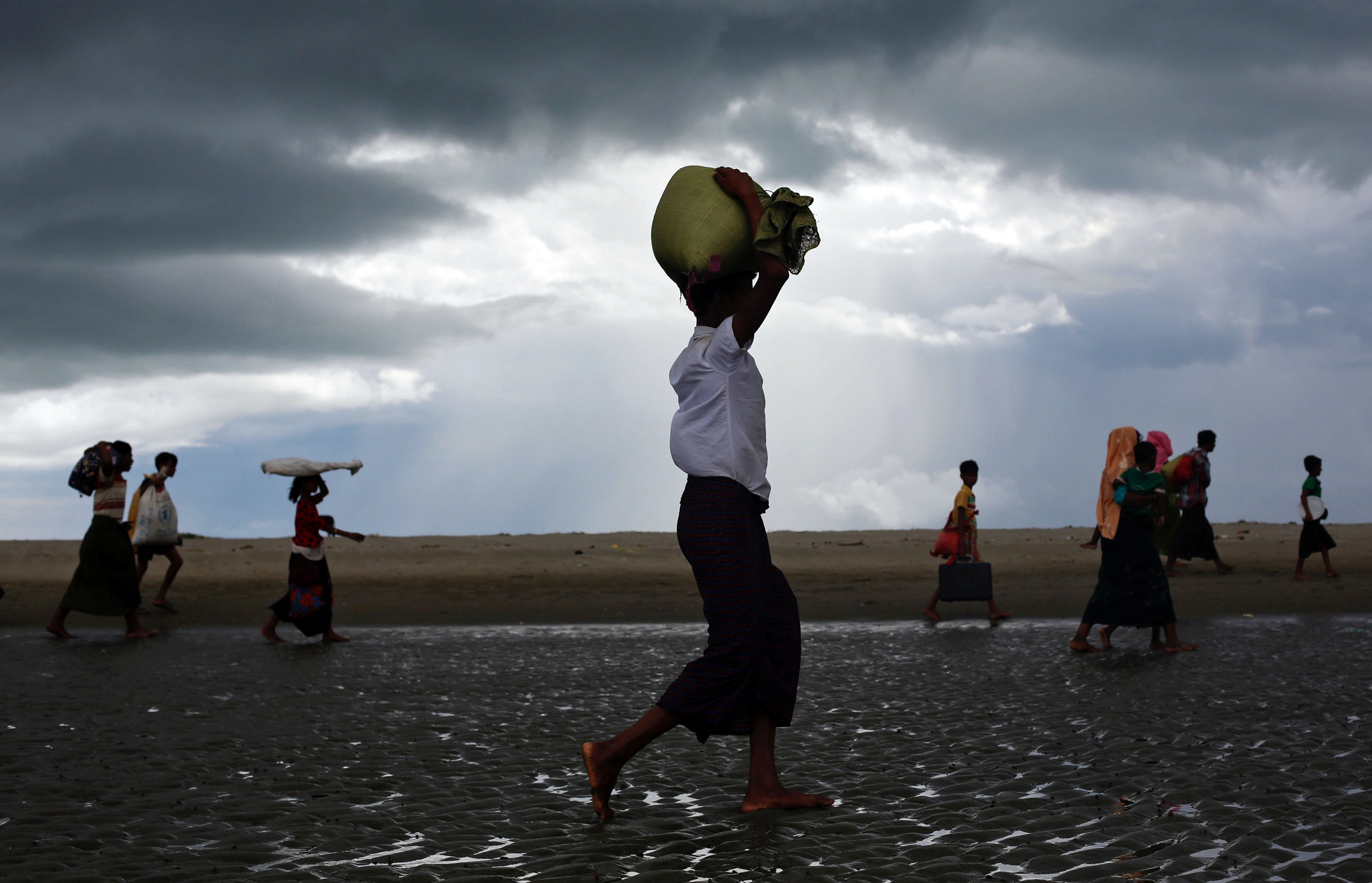 Rohingya refugees walk on the shore after crossing the Bangladesh-Myanmar border by boat through the Bay of Bengal in Shah Porir Dwip, Bangladesh September 11, 2017. REUTERS/Danish Siddiqui