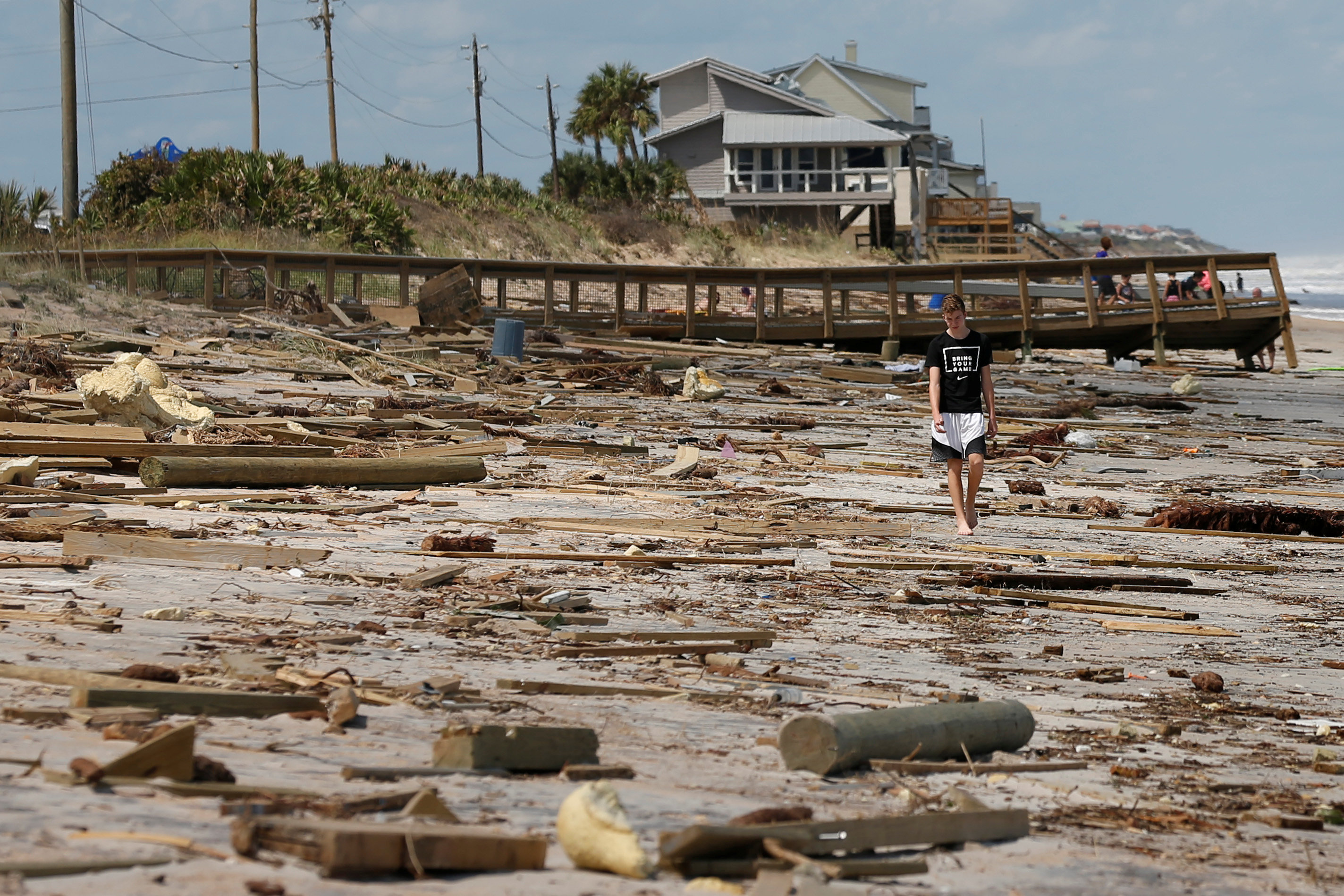 A boy walks amongst debris on the beach after Hurricane Irma passed the area in Ponte Vedra Beach, Florida, U.S., September 12, 2017. REUTERS/Chris Wattie