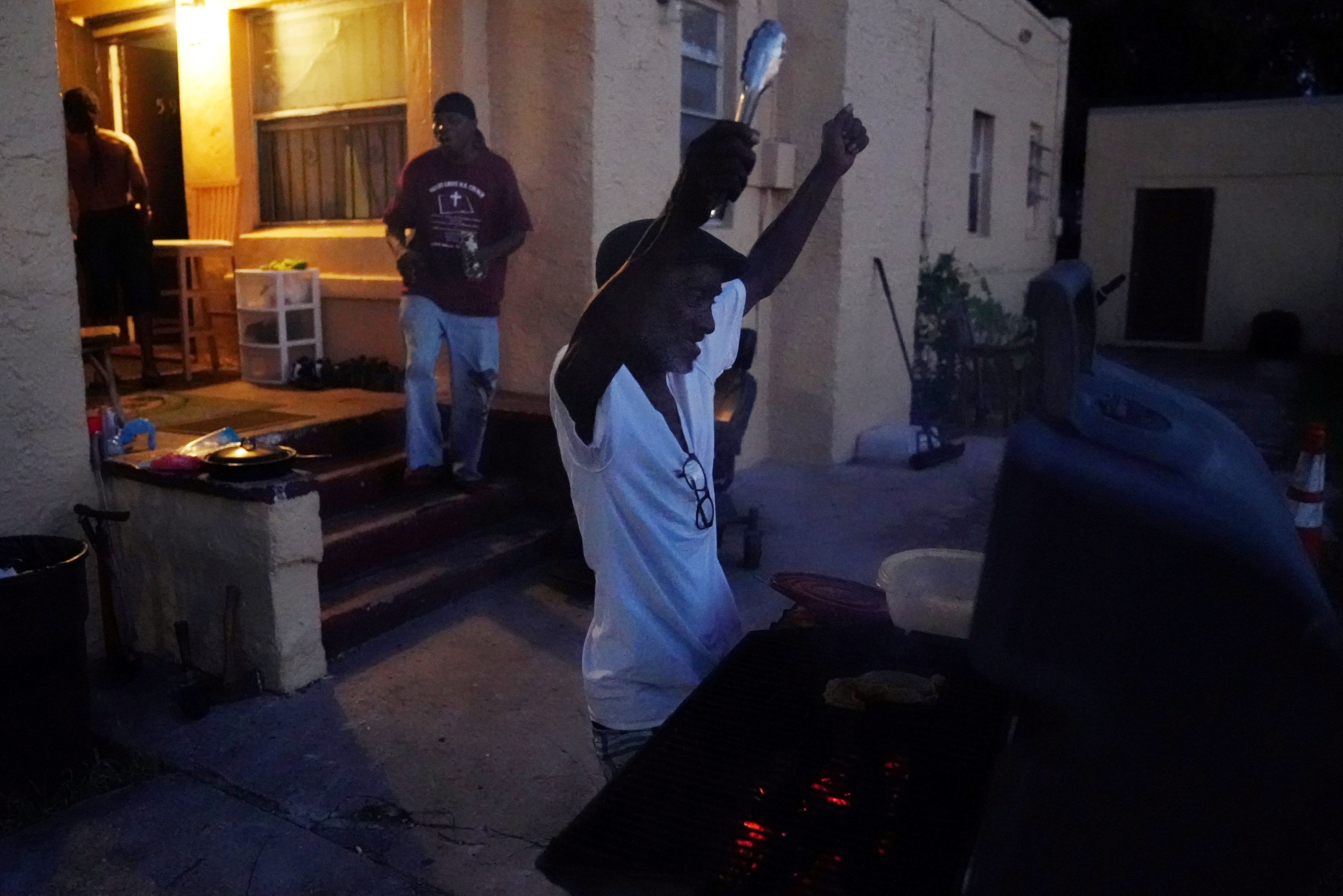 A man cheers just as power is restored to his house after Hurricane Irma struck the Little Haiti neighborhood of Miami, Florida, U.S., September 12, 2017. REUTERS/Carlo Allegri