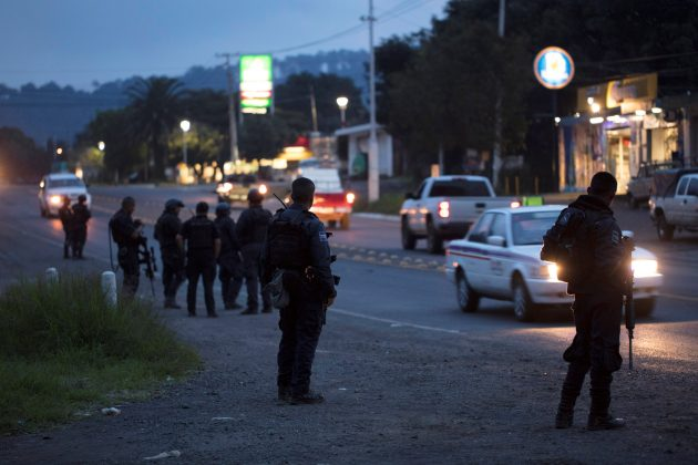 Police officers stand guard as they carry out inspections at a checkpoint after 13 people were killed in battles between rival gangs in two states in central and western Mexico, in Uruapan, in the state of Michoacan, Mexico, September 13, 2017. REUTERS/Alan Ortega