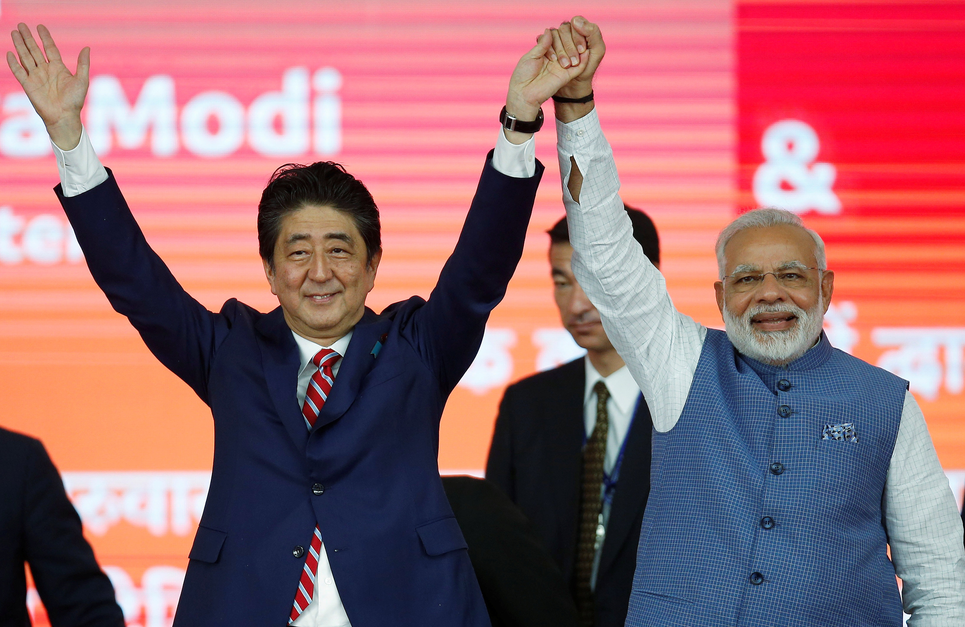 Japanese Prime Minister Shinzo Abe (L) and his Indian counterpart Narendra Modi raise hands after the groundbreaking ceremony for a high-speed rail project in Ahmedabad, India, September 14, 2017. REUTERS/Amit Dave