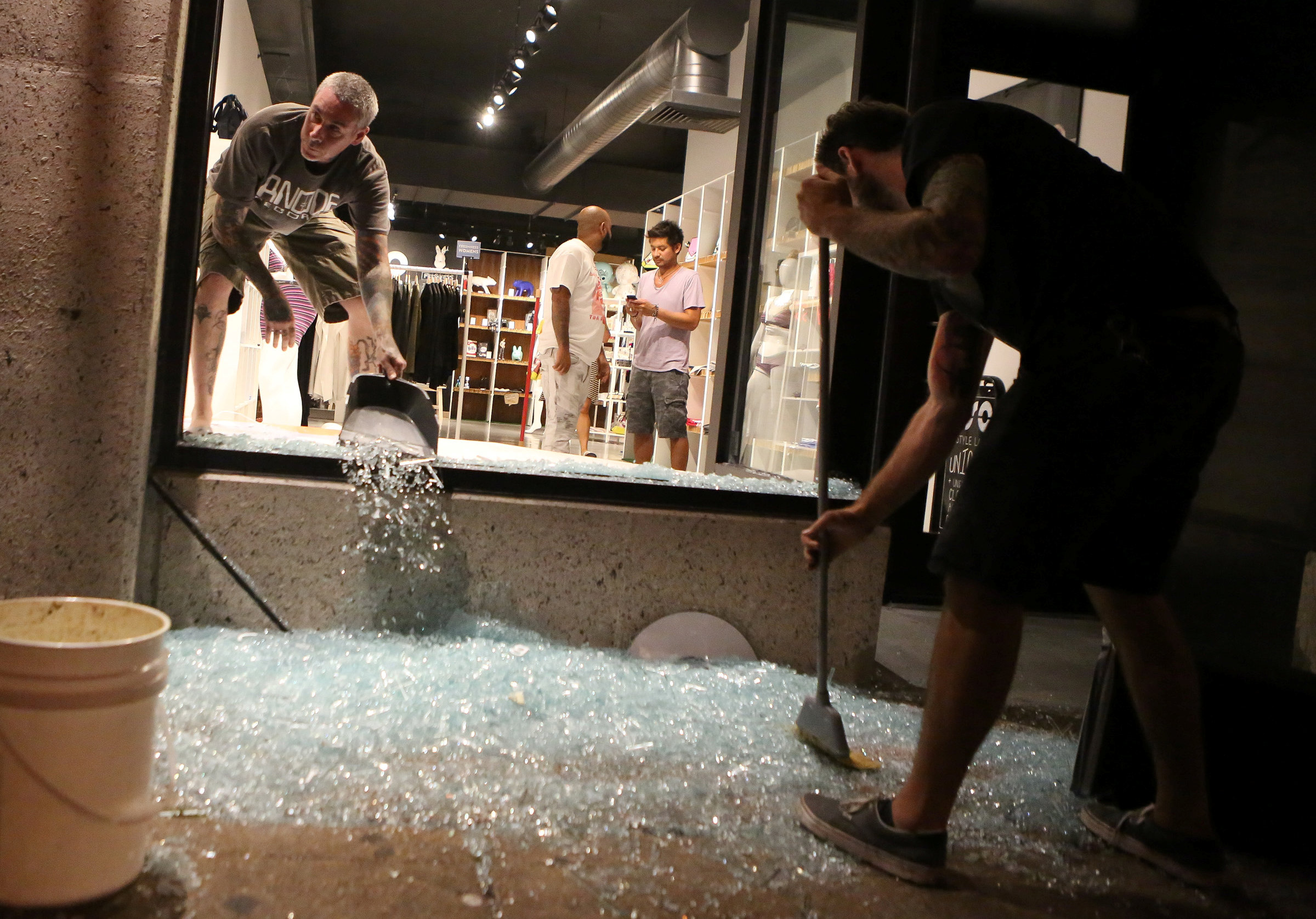 Shopkeepers clean up shattered glass during the second night of demonstrations after a not guilty verdict in the murder trial of former St. Louis police officer Jason Stockley, charged with the 2011 shooting of Anthony Lamar Smith, who was black, in St. Louis, Missouri, U.S., September 16, 2017.
