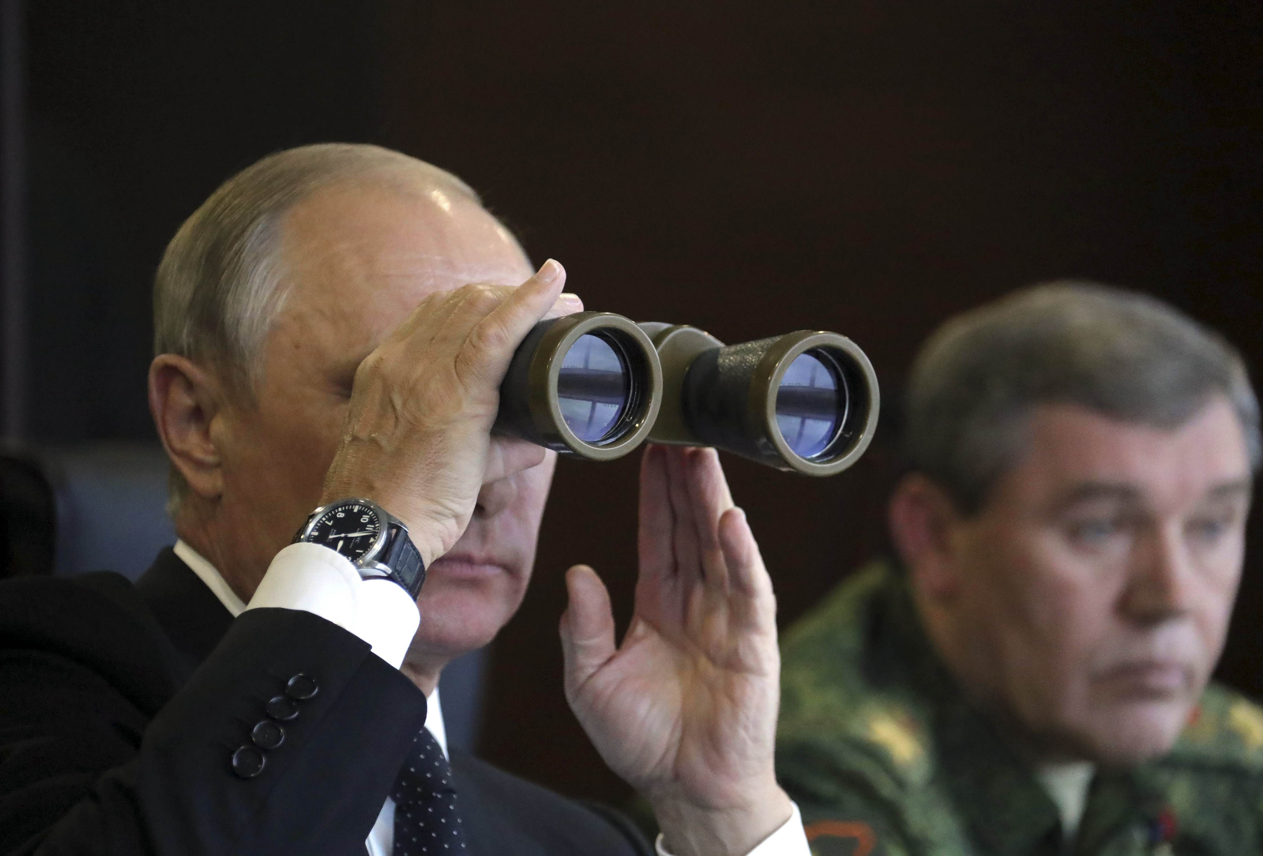 Russian President Vladimir Putin uses a pair of binoculars while watching the Zapad-2017 war games, held by Russian and Belarussian servicemen, with Chief of the General Staff of Russian Armed Forces Valery Gerasimov seen nearby, at a military training ground in the Leningrad region, Russia September 18, 2017.