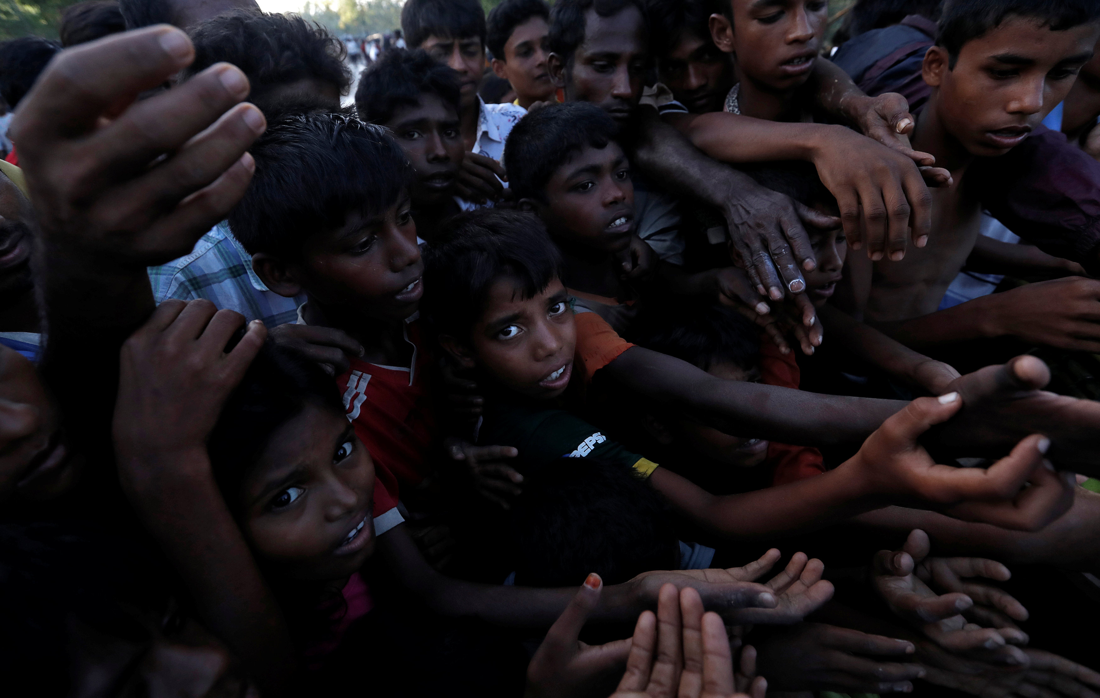 People reach out during the distribution of bananas in a Rohingya refugee camp in Cox's Bazar, Bangladesh, September 17, 2017.