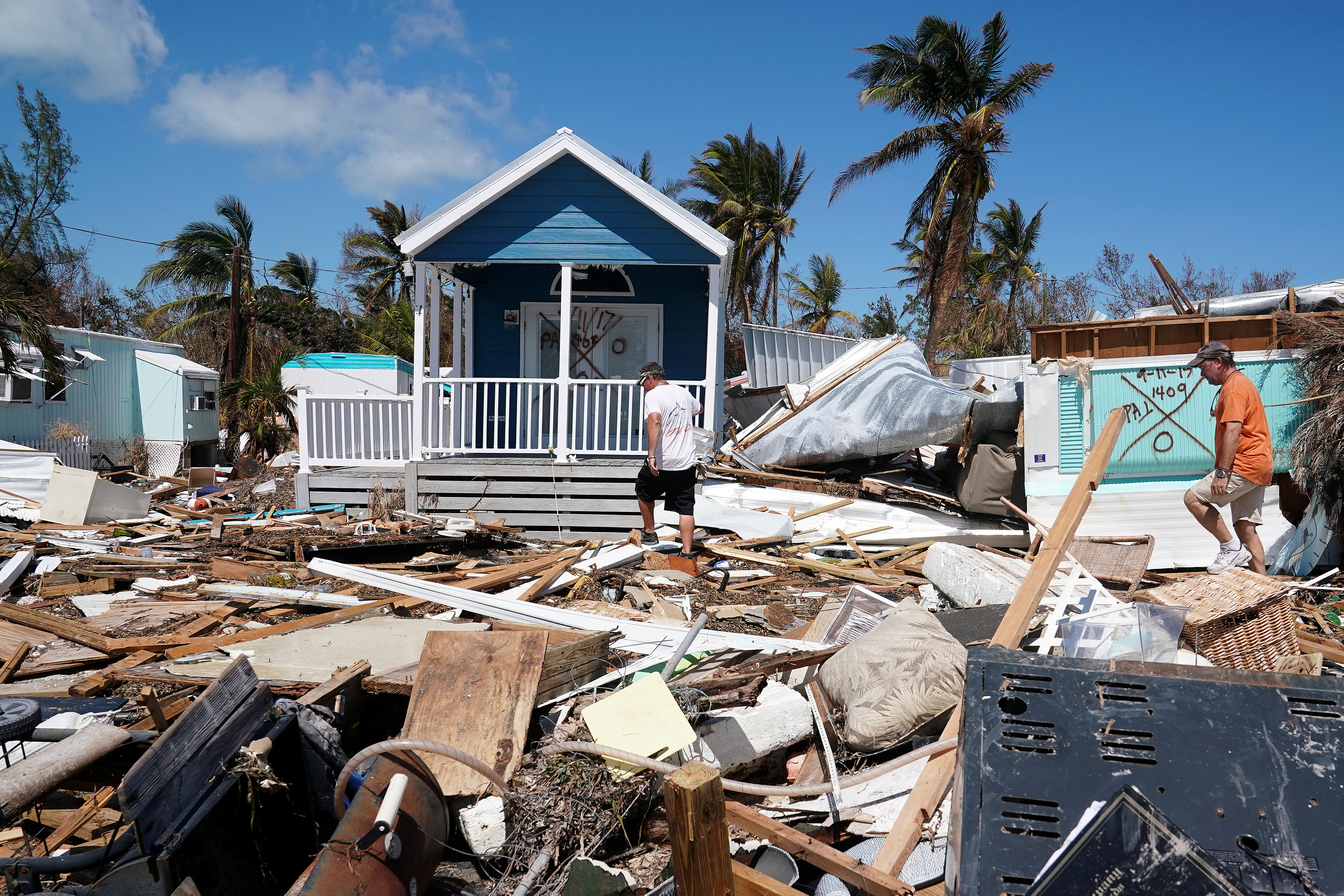 Residents walk though a debris field of former houses following Hurricane Irma in Islamorada, Florida, U.S., September 15, 2017. REUTERS/Carlo Allegri