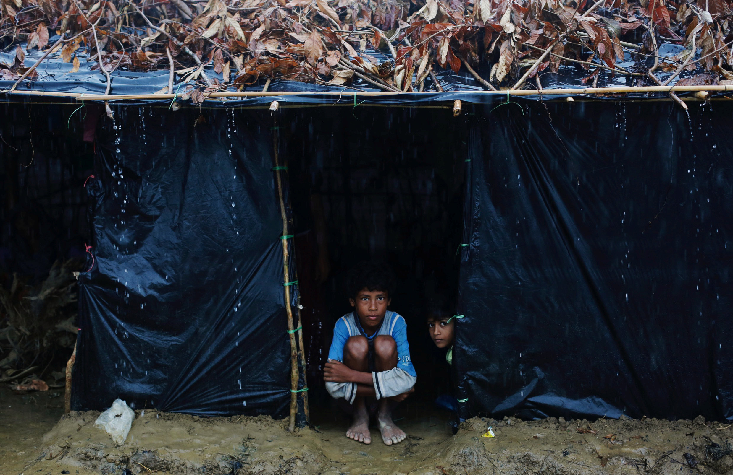 Rohingya refugees sit inside their temporary shelter as it rains at a camp in Cox's Bazar, Bangladesh September 19, 2017. REUTERS/Danish Siddiqui