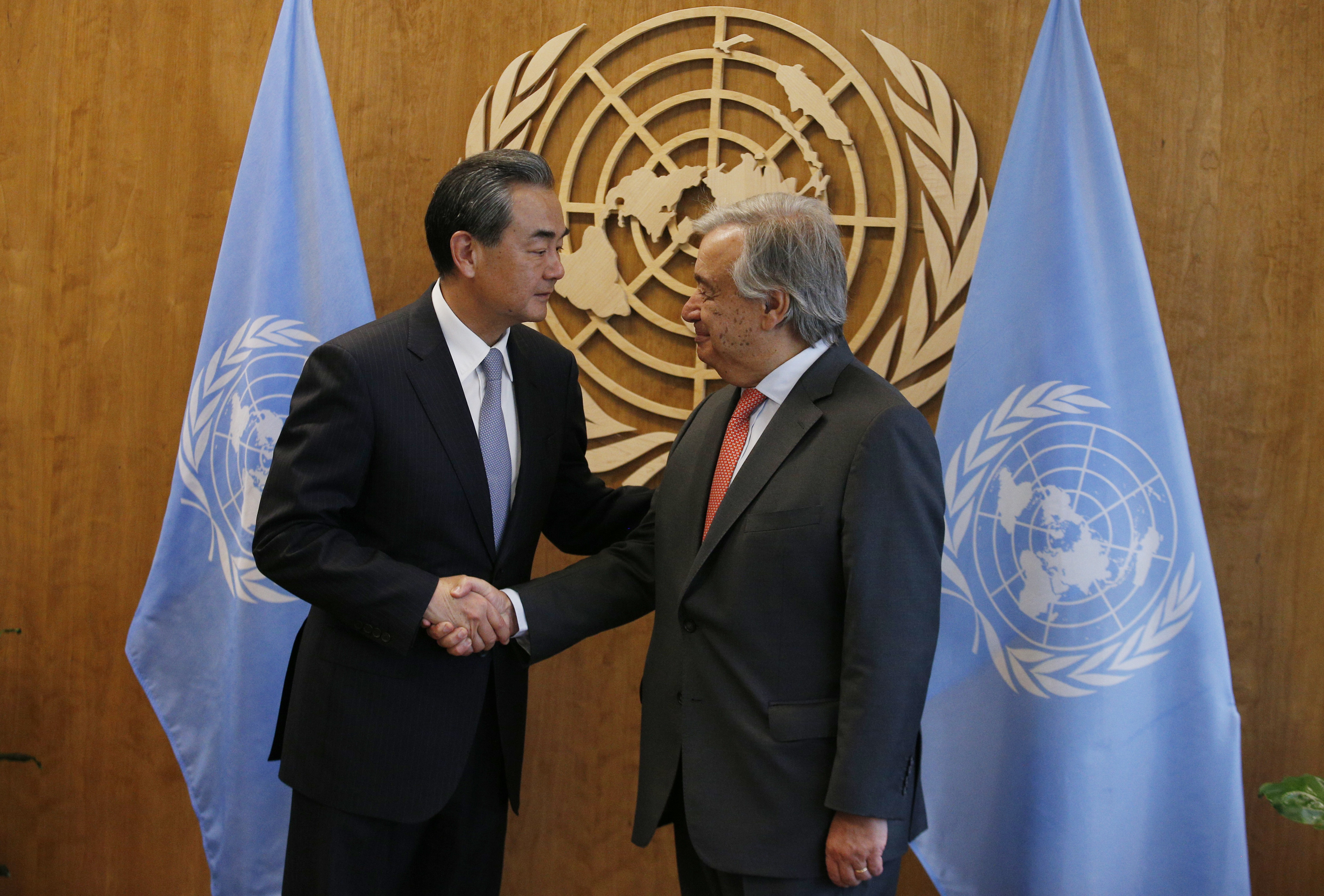 FILE PHOTO: Chinese Foreign Minister Wang Yi (L) shakes hands with United Nations Secretary General Antonio Guterres prior to their meeting at U.N. headquarters in New York, U.S., September 18, 2017. REUTERS/Brendan McDermid