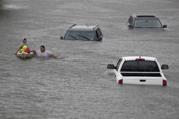 FILE PHOTO: Jesus Rodriguez rescues Gloria Garcia after rain from Hurricane Harvey flooded Pearland, in the outskirts of Houston, Texas, U.S. August 27, 2017. REUTERS/Adrees Latif/File Photo