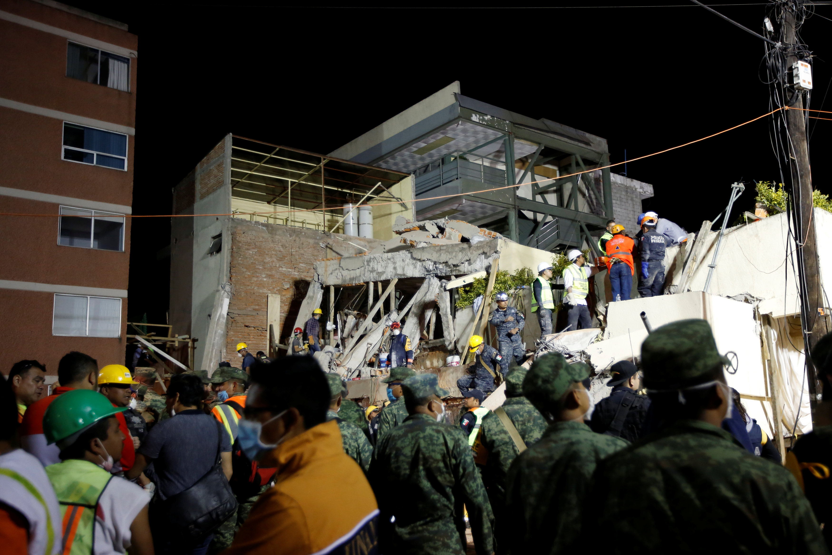 Rescue workers search through rubble during a floodlit search for students at Enrique Rebsamen school in Mexico City, Mexico September 20, 2017. REUTERS/Carlos Jasso