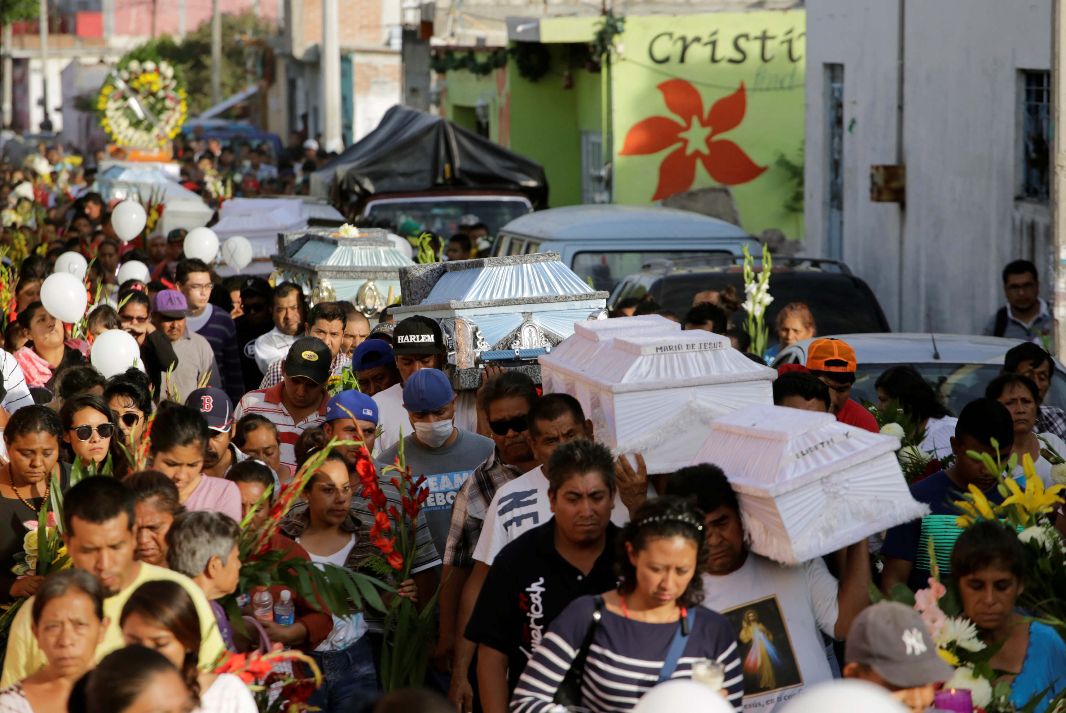 People accompany caskets, holding the bodies of victims who died in an earthquake, through the streets in Atzala, on the outskirts of Puebla, Mexico September 20, 2017.