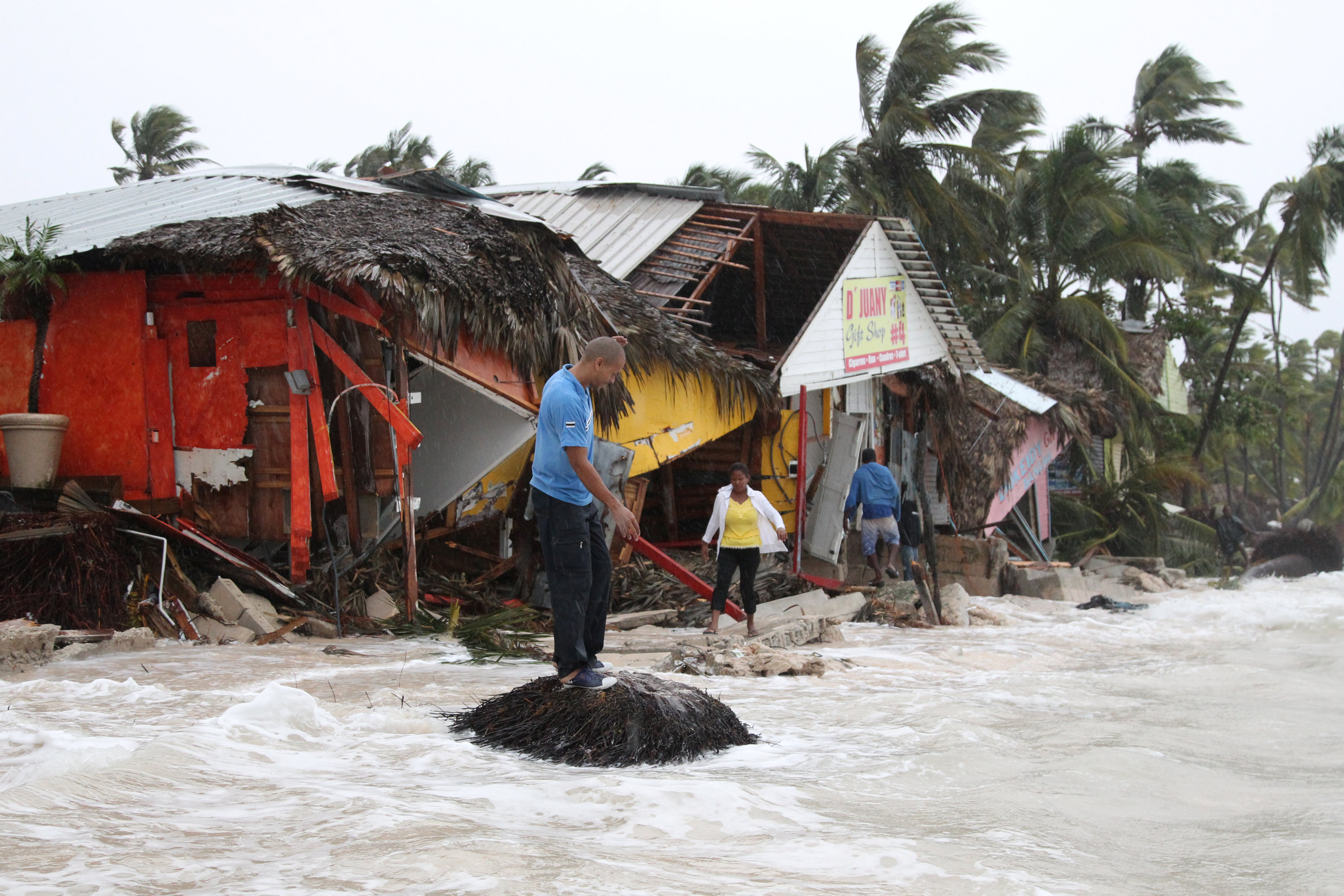 People walk among debris on the seashore in the aftermath of Hurricane Maria in Punta Cana, Dominican Republic, September 21, 2017. REUTERS/Ricardo Rojas