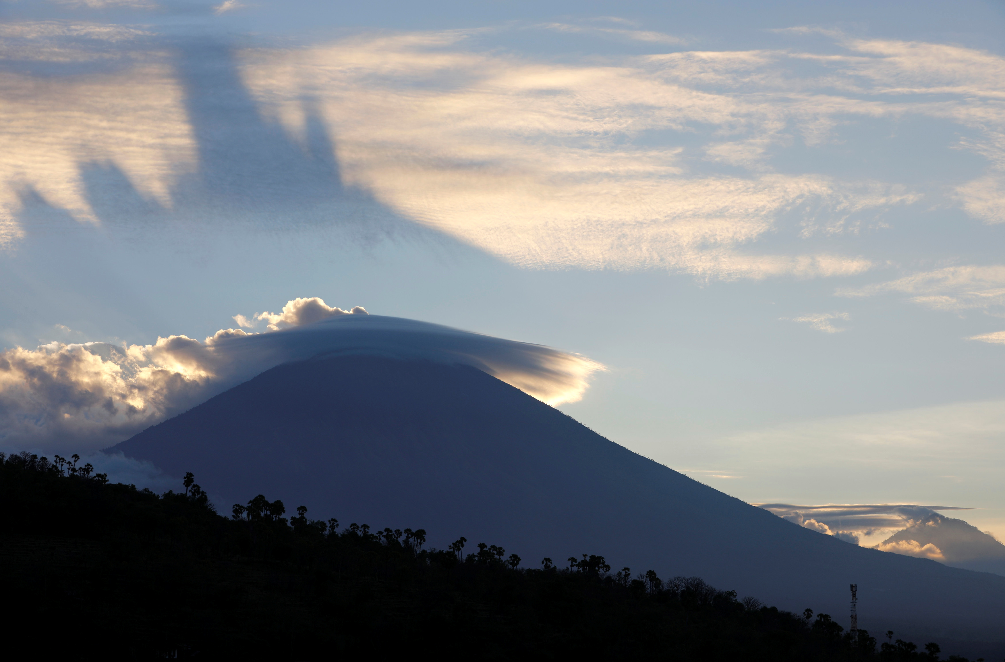 The sun sets behind Mount Agung, a volcano on the highest alert level, from Amed on the resort island of Bali, Indonesia September 25, 2017.