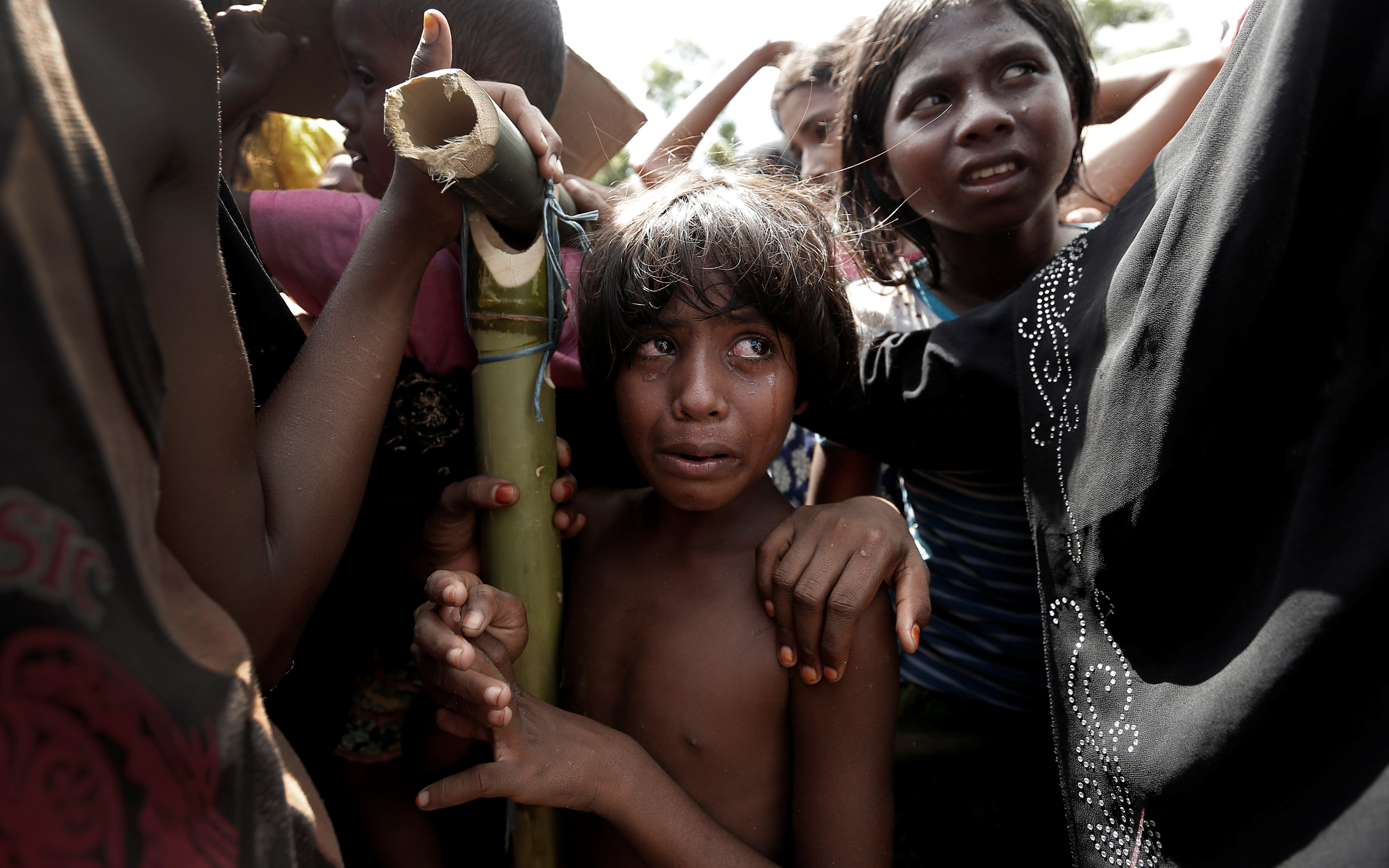 A Rohingya refugee girl reacts as people scuffle while waiting to receive aid in Cox's Bazar, Bangladesh, September 25, 2017.