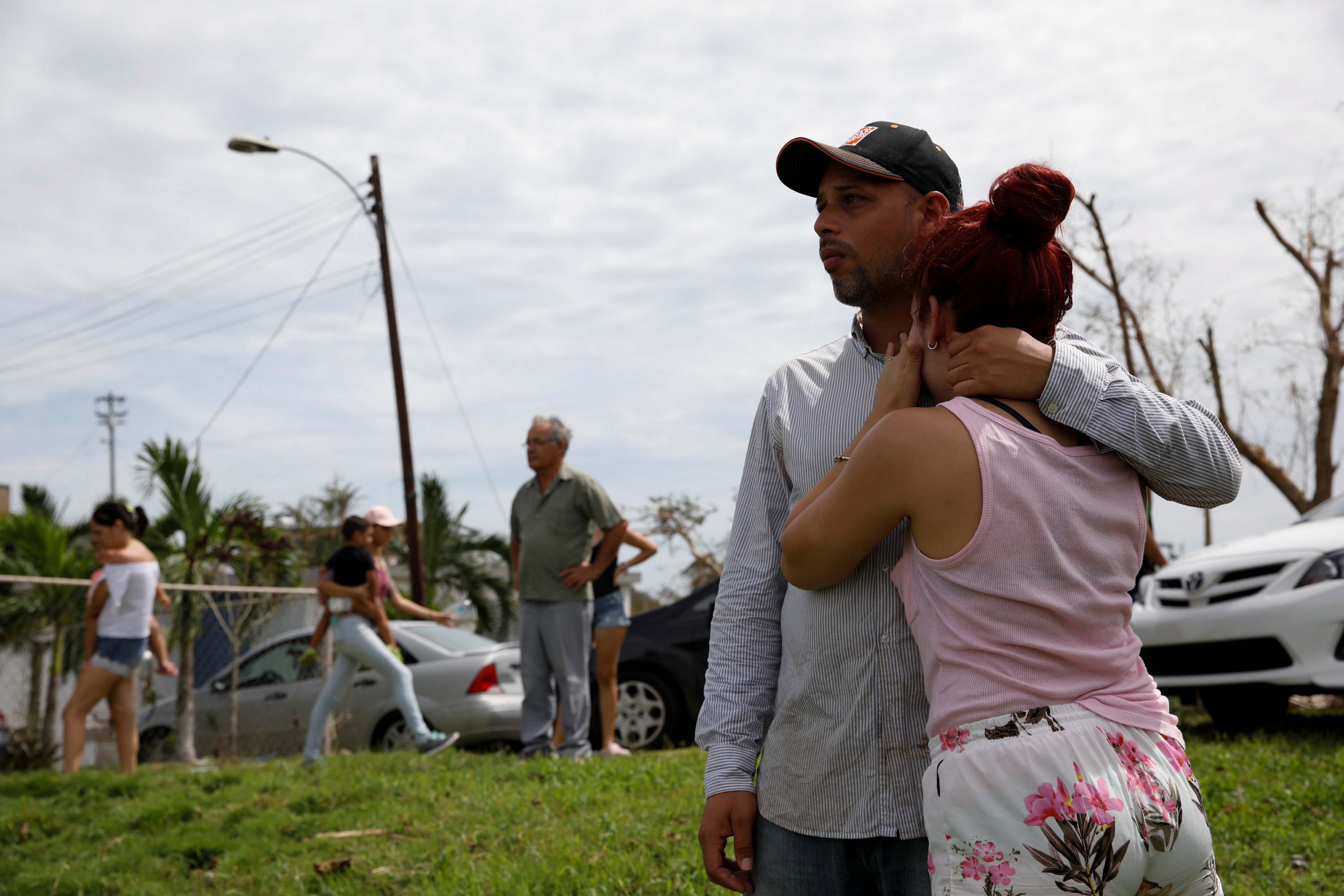 Local residents react while they look at the water flowing over the road at the dam of the Guajataca lake.