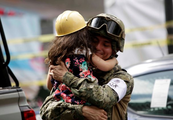 A girl hugs a Mexican marine officer as she offers hugs to people near the site of a collapsed building after an earthquake, in Mexico City.