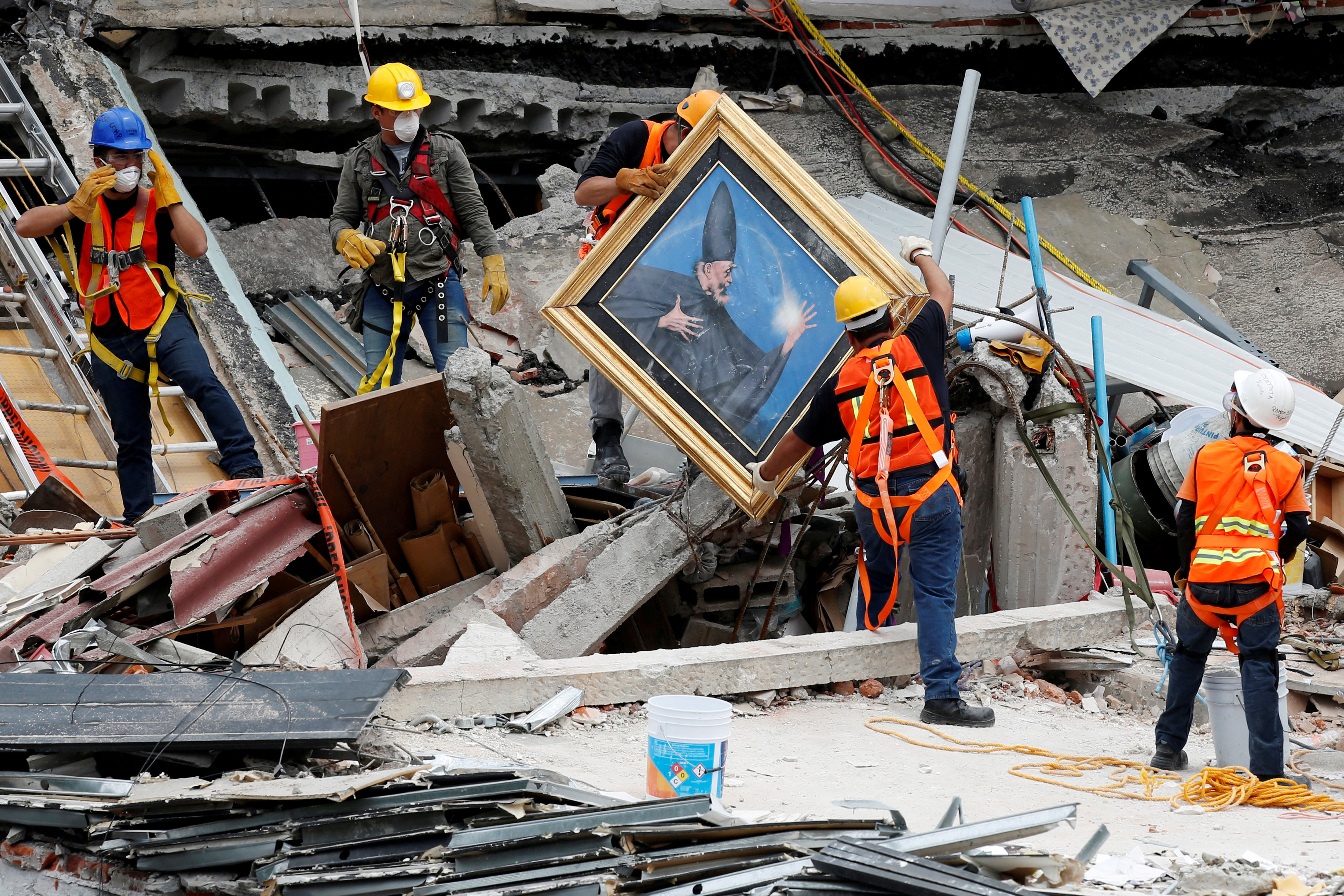 Mexican and international rescue teams remove a painting as they search for survivors in a collapsed building after an earthquake, at Roma neighborhood in Mexico City.