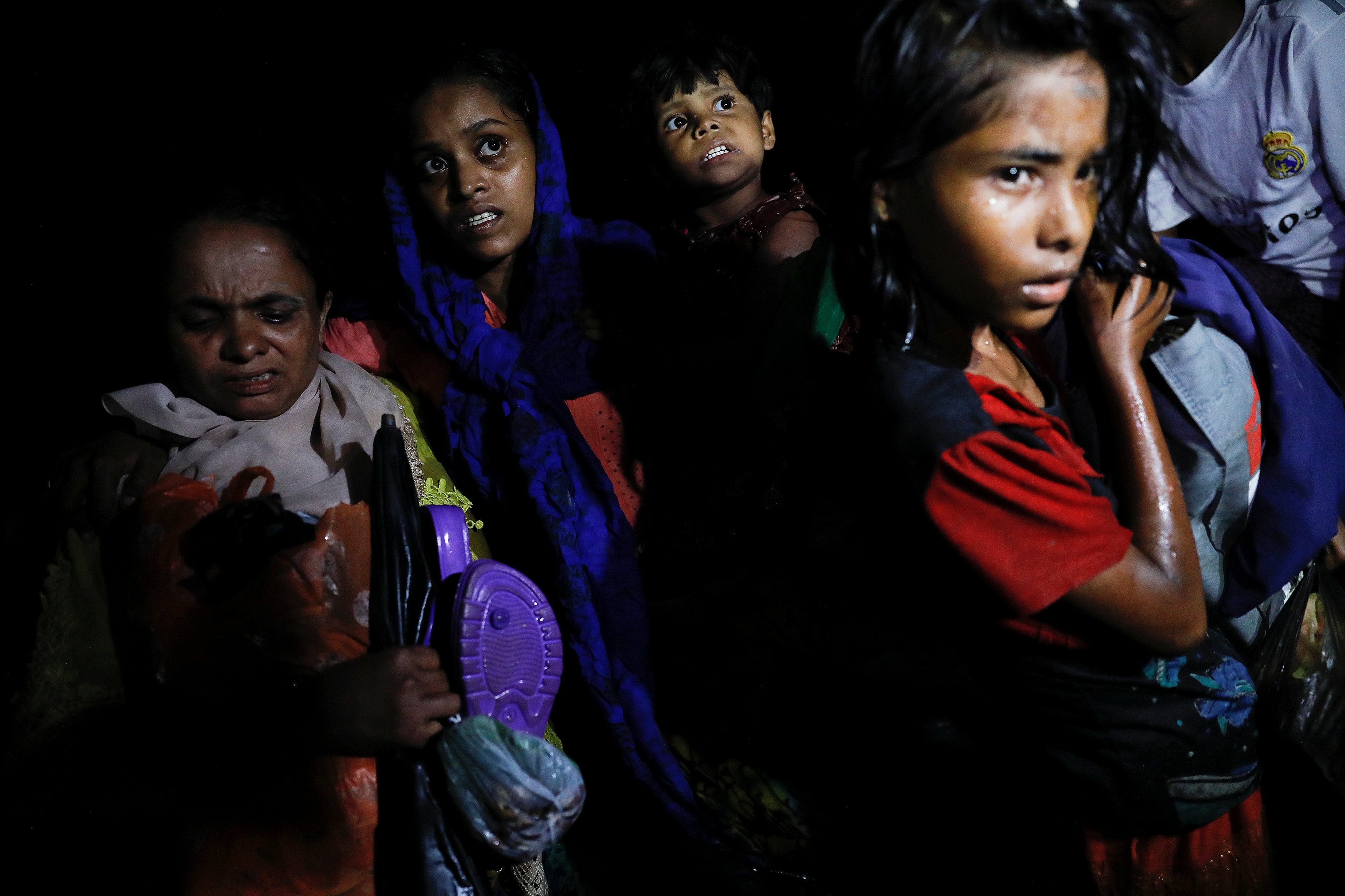 Women carry children through the water as hundreds of Rohingya refugees arrive under the cover of darkness by wooden boats from Myanmar to the shore of Shah Porir Dwip, in Teknaf, near Cox's Bazar in Bangladesh, September 27, 2017. Picture taken September 27, 2017. REUTERS/Damir Sagolj