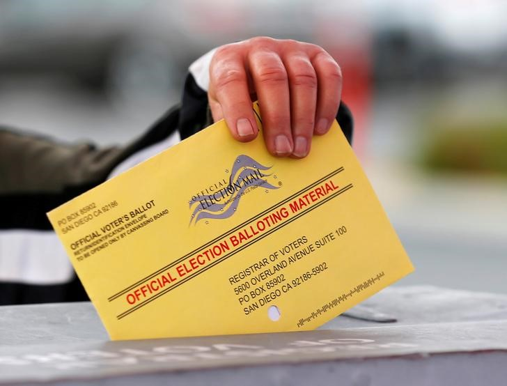FILE PHOTO - A poll worker places a mail-in ballot into a voting box as voters drop off their ballot in the U.S. presidential primary election in San Diego, California, United States, June 7, 2016. REUTERS/Mike Blake/File Photo
