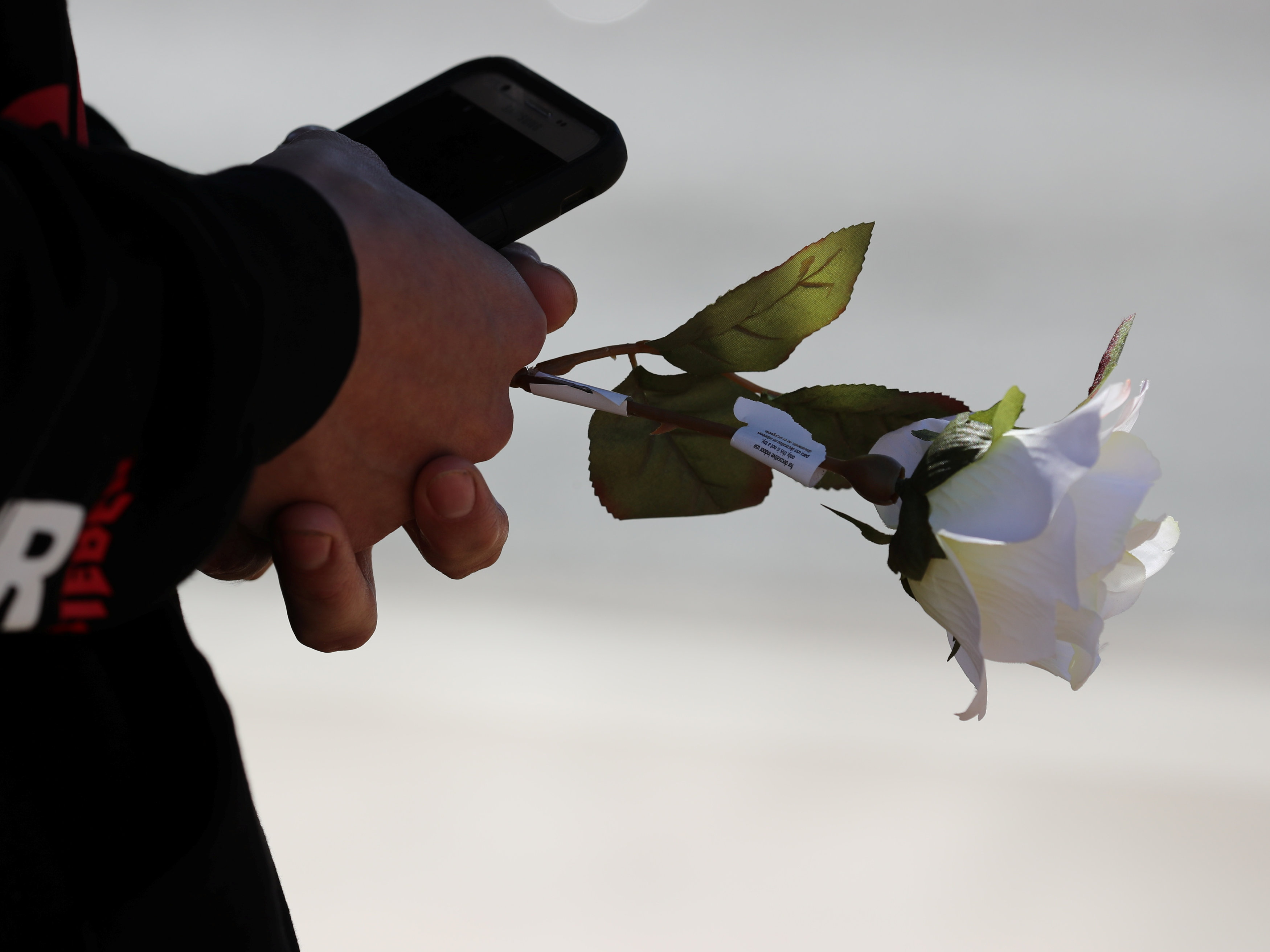 A man holds a white rose outside a police perimeter near the scene of the Route 91 music festival mass shooting in Las Vegas, Nevada, U.S., October 2, 2017. REUTERS/Mike Blake