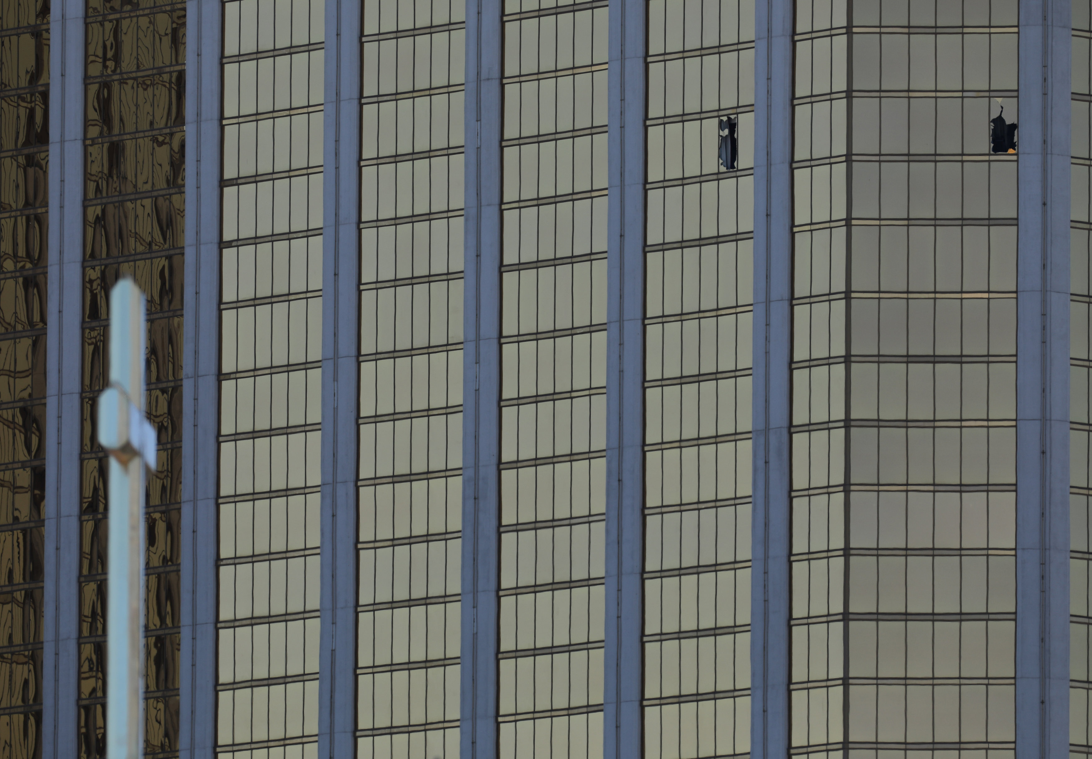Two broken windows are seen at The Mandalay Bay Resort and Casino and a cross atop a church next to the concert grounds near the scene of a mass shooting at the Route 91 Festival in Las Vegas, Nevada, U.S., October 2, 2017. REUTERS/Mike Blake