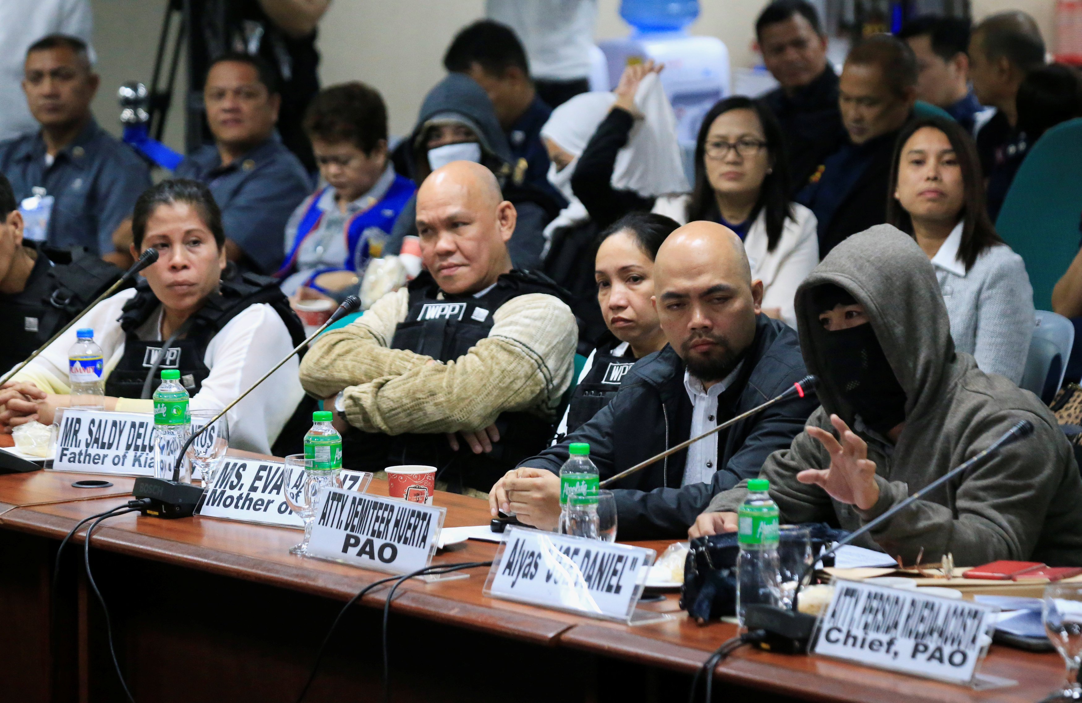 A witness to a recent teen killing linked to illegal drugs, wearing a sweatshirt and mask to hide his identity gestures while parents of the killed teenager, wearing bulletproof vests listen during the Senate investigation on illegal drugs at the Senate headquarters in Pasay city, metro Manila, Philippines October 2, 2017. REUTERS/Romeo Ranoco