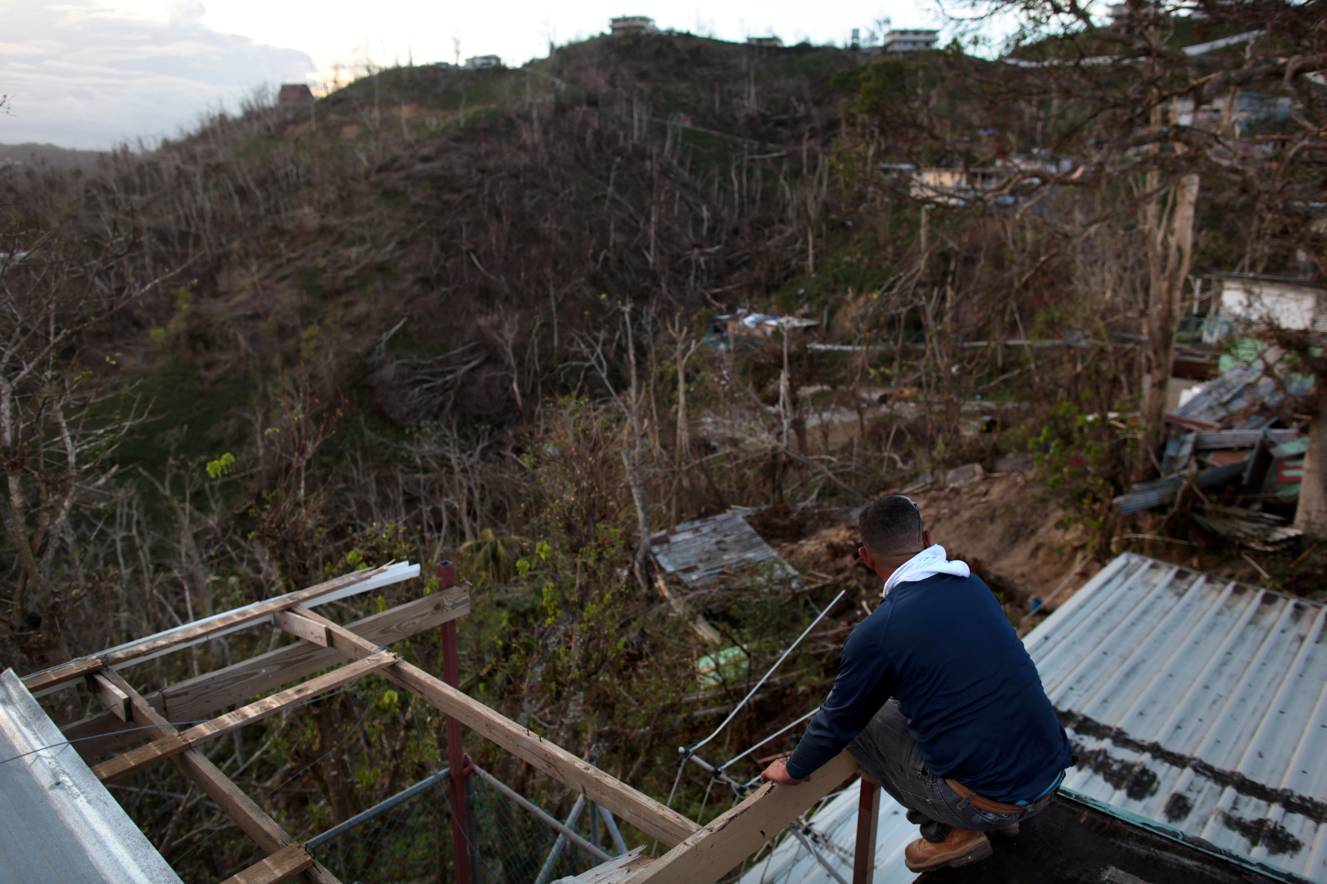A local resident sits on the roof of his home that was damaged by Hurricane Maria in Guaynabo, Puerto Rico, October 2, 2017. REUTERS/Alvin Baez