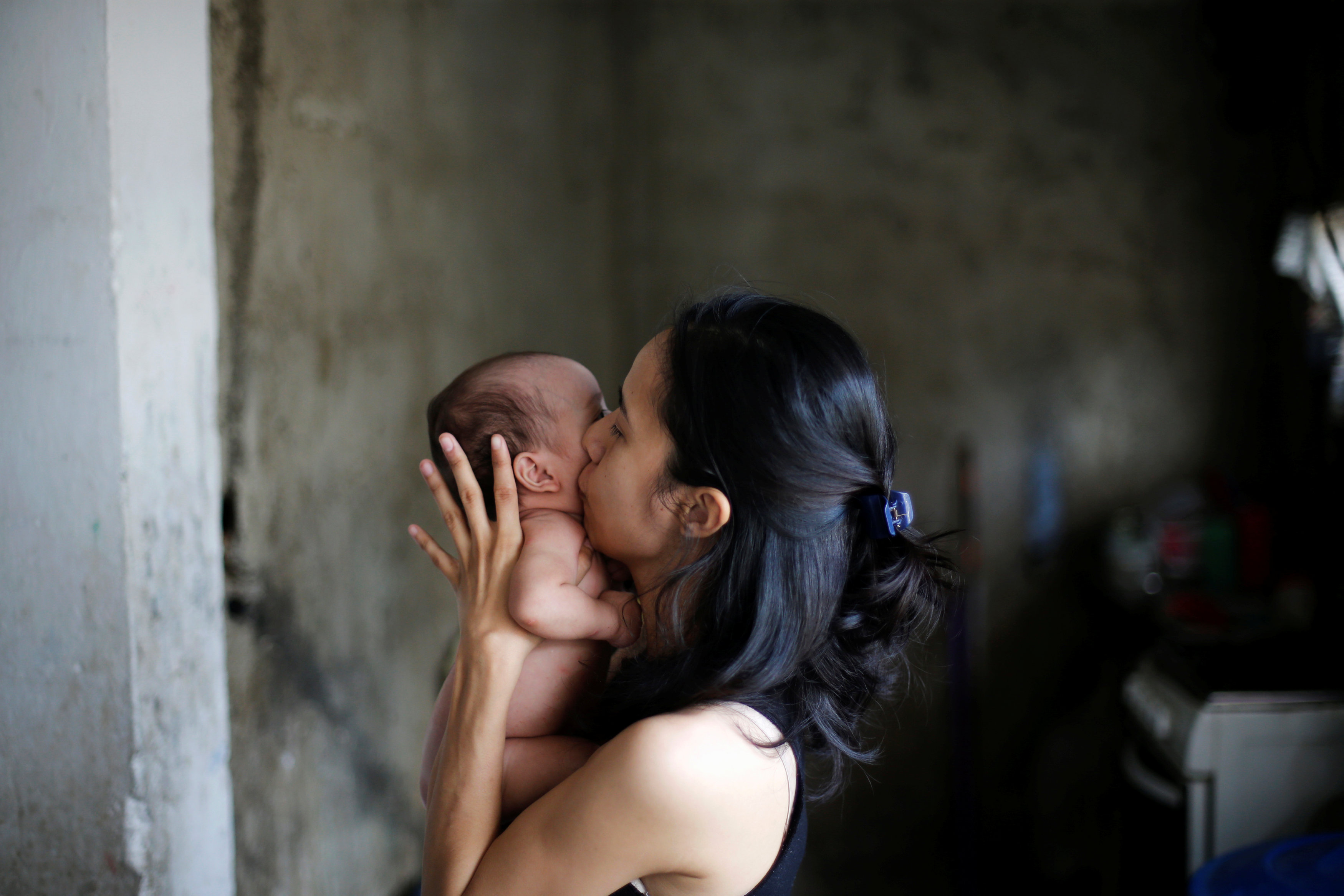 Yennifer Padron kisses her baby in her house at Petare slum in Caracas. REUTERS/Andres Martinez Casares