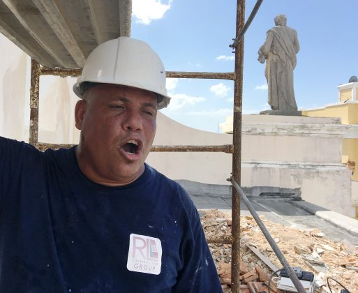 Jesus Santos sings operatic love songs while repairing plaster to a Hurricane Maria damaged facade at Cathedral of San Juan Bautista in San Juan, Puerto Rico on October 4, 2017. Picture taken on October 4, 2017. REUTERS/Hugh Bronstein
