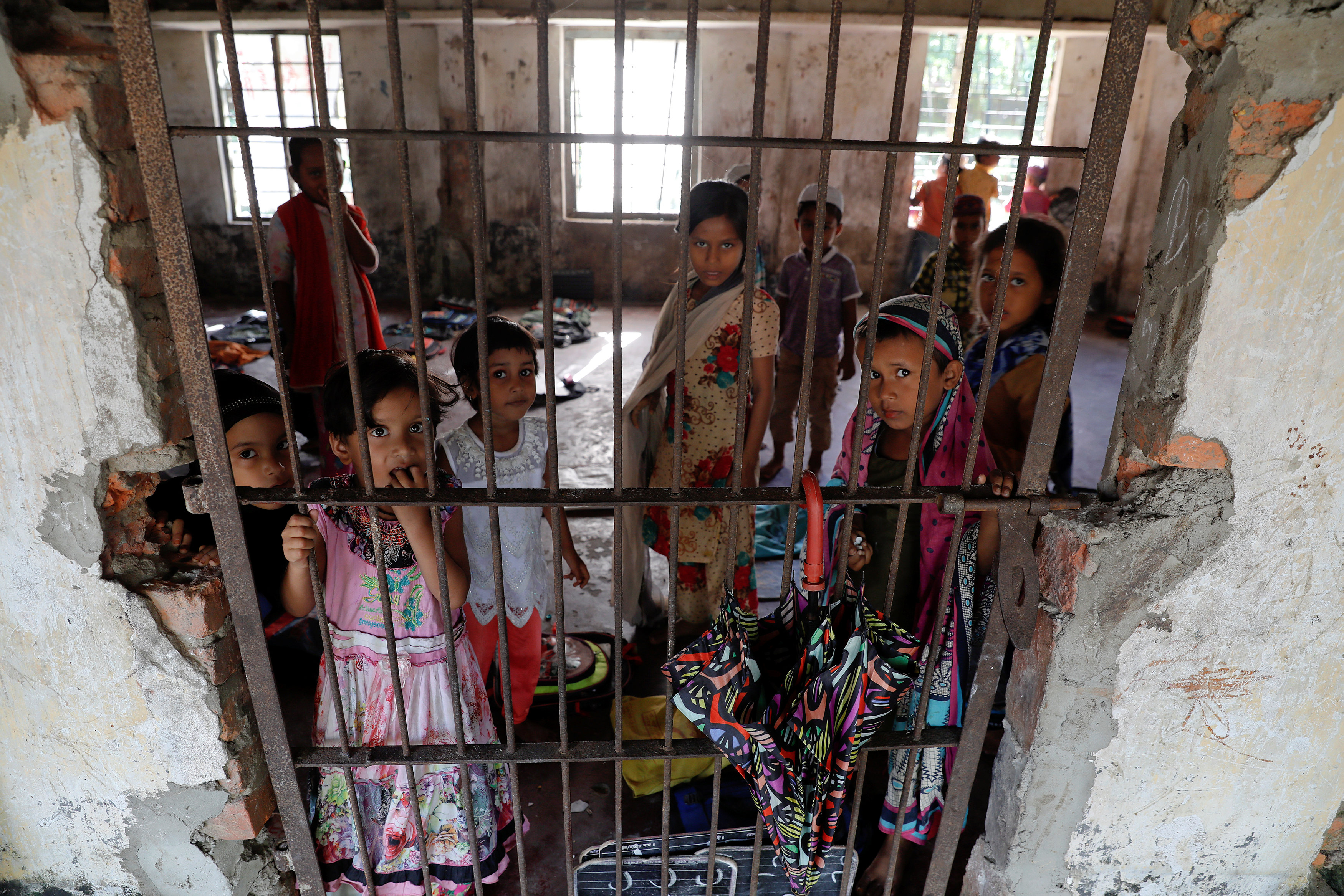 Students of a local madrasa watch from inside their classroom as bodies of Rohingya refugees from Myanmar, who were killed when their boat capsized on the way to Bangladesh, are brought to their school in Shah Porir Dwip, in Teknaf, near Cox's Bazar in Bangladesh, October 9, 2017.