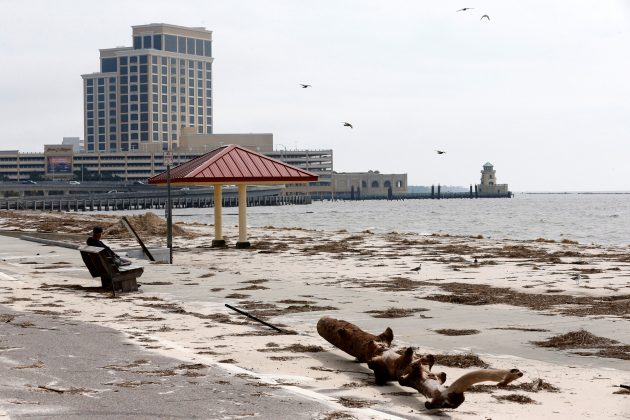A man sits on a bench overlooking a beach covered in debris scattered by Hurricane Nate, in Biloxi, Mississippi, U.S.,