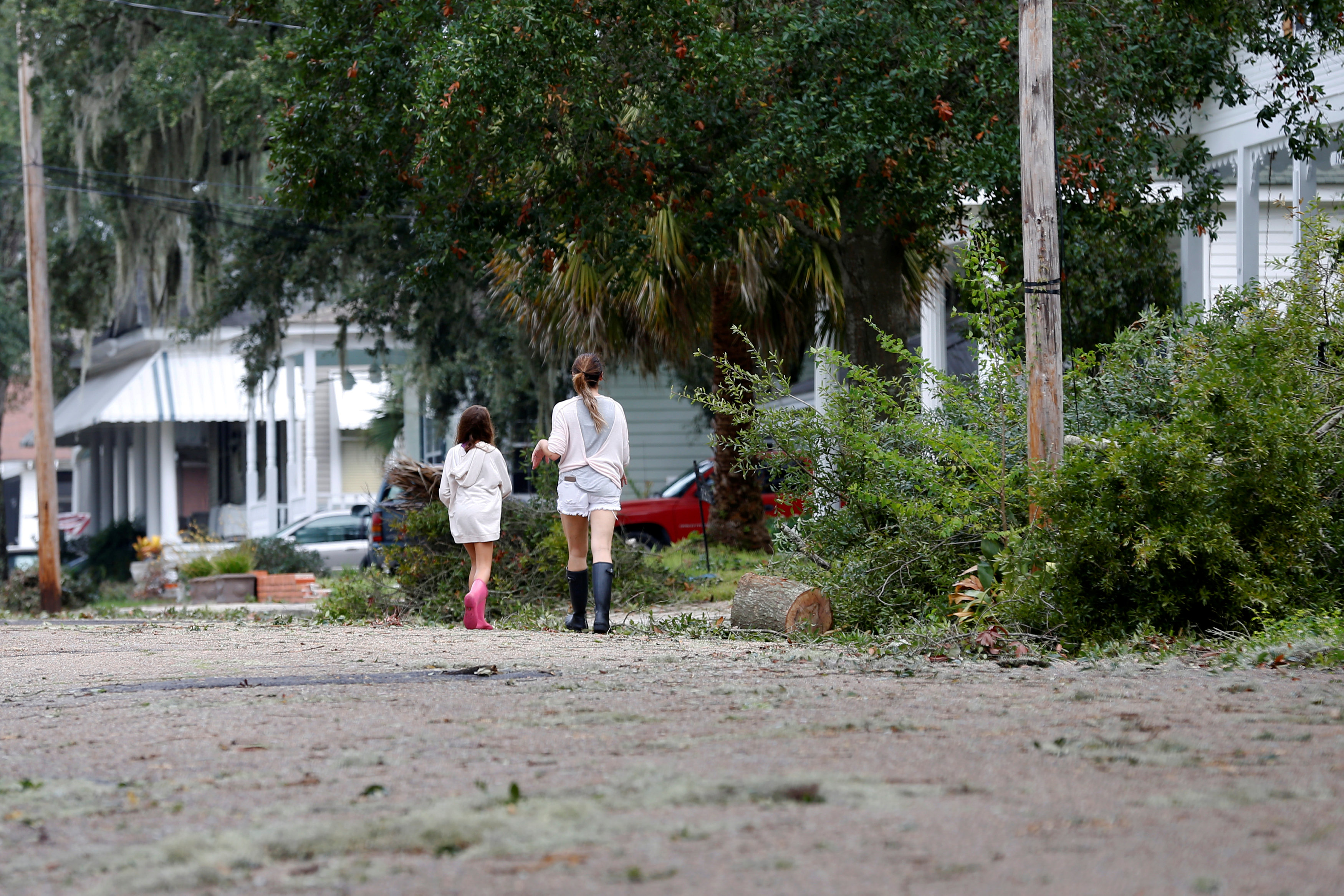 Residents walk down a street covered in debris scattered by Hurricane Nate, in Biloxi, Mississippi, U.S., October 8, 2017.