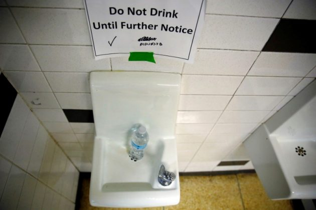 A sign is seen next to a water dispenser at North Western High School in Flint, a city struggling with the effects of lead-poisoned drinking water in Michigan, May 4, 2016.