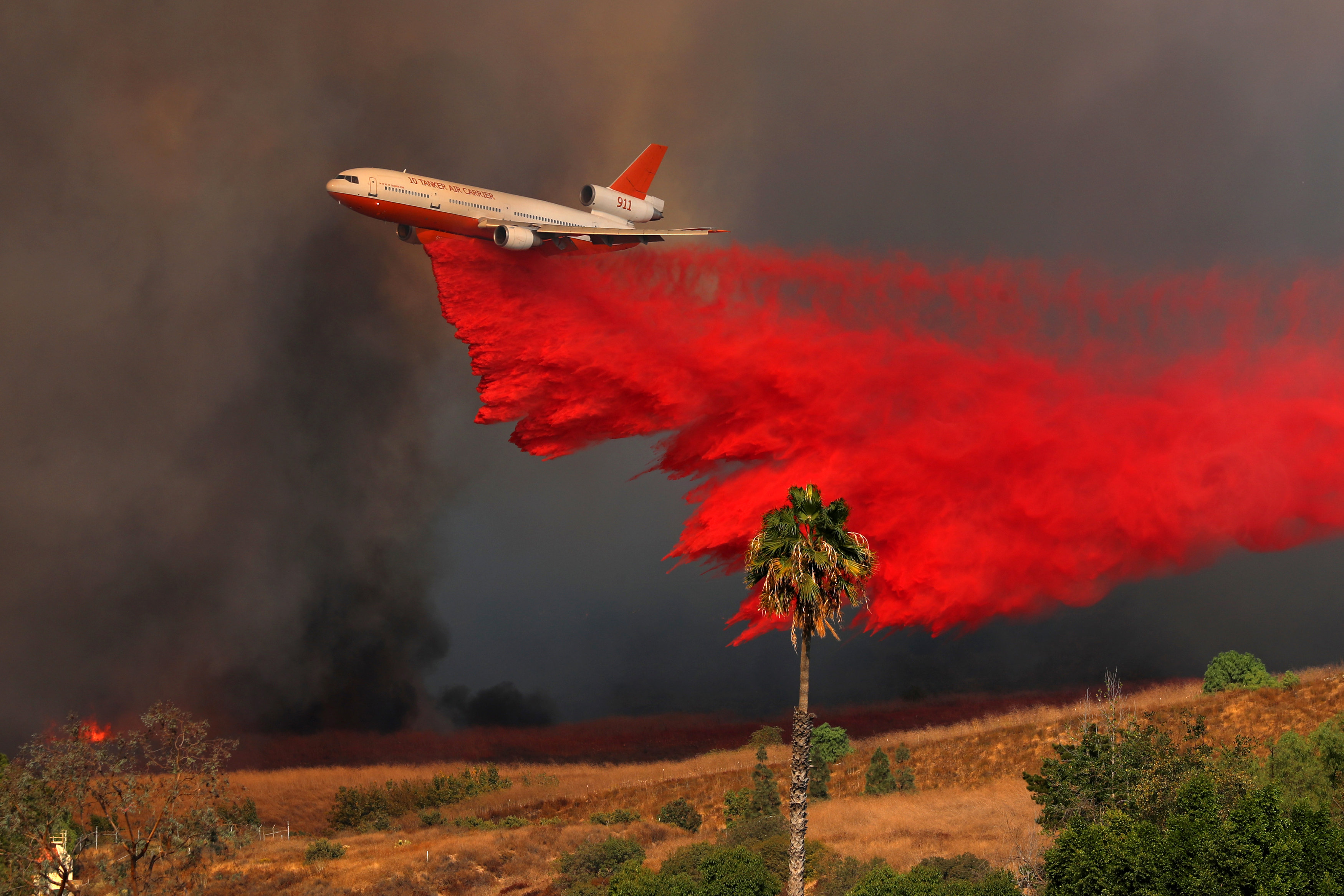 A DC-10 aircraft drops fire retardant on a wind driven wildfire in Orange, California, U.S., October 9, 2017.