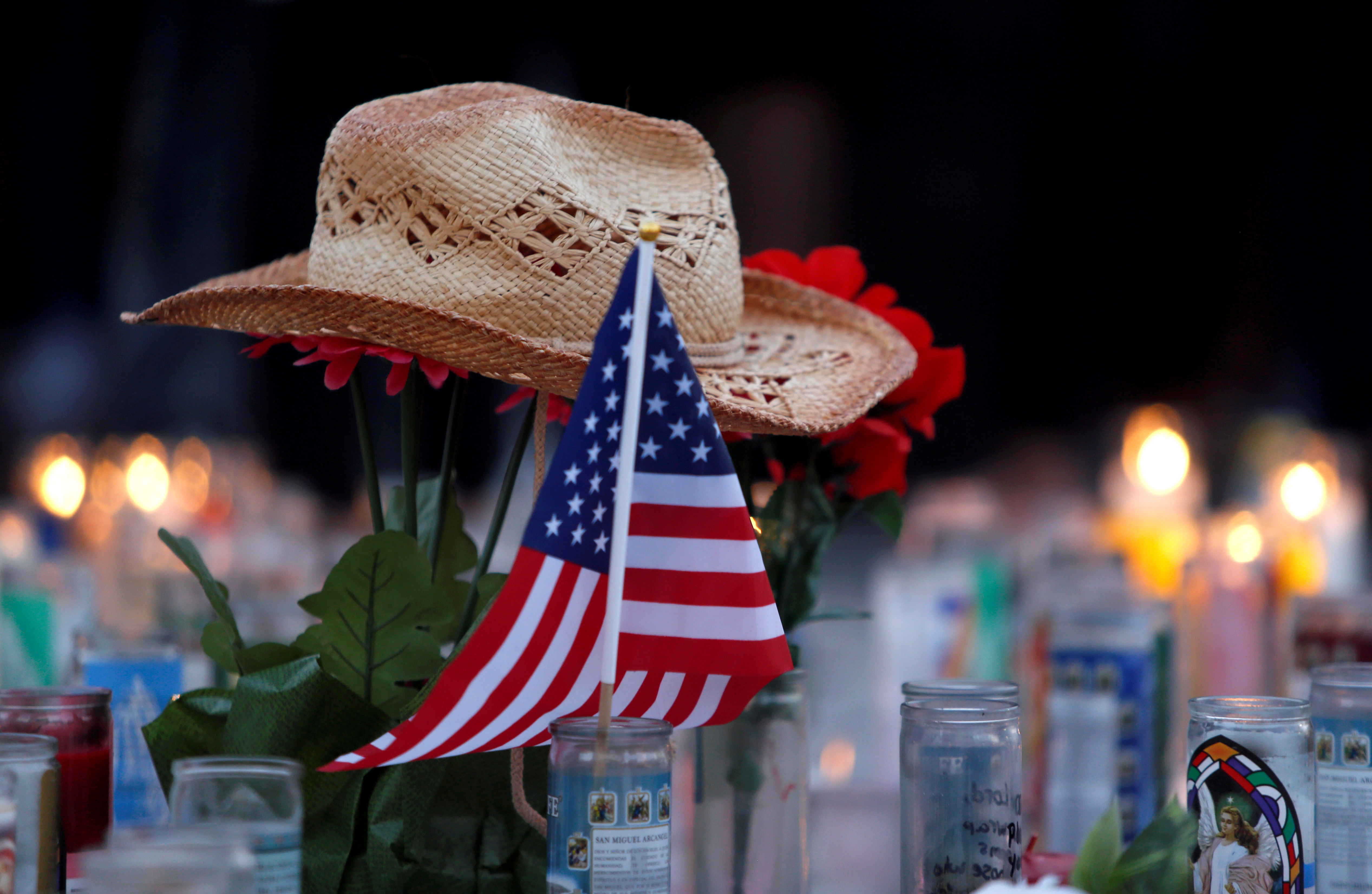 A hat rests on flowers in a makeshift memorial during a vigil marking the one-week anniversary of the October 1 mass shooting in Las Vegas, Nevada U.S. October 8, 2017. REUTERS/Las Vegas Sun/Steve Marcus